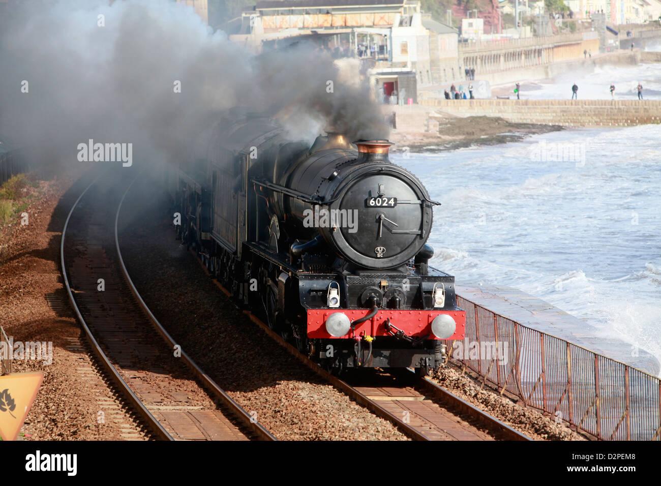 A vintage steam locomotive passes through Dawlish on the famous Brunel railway line - Stock Image