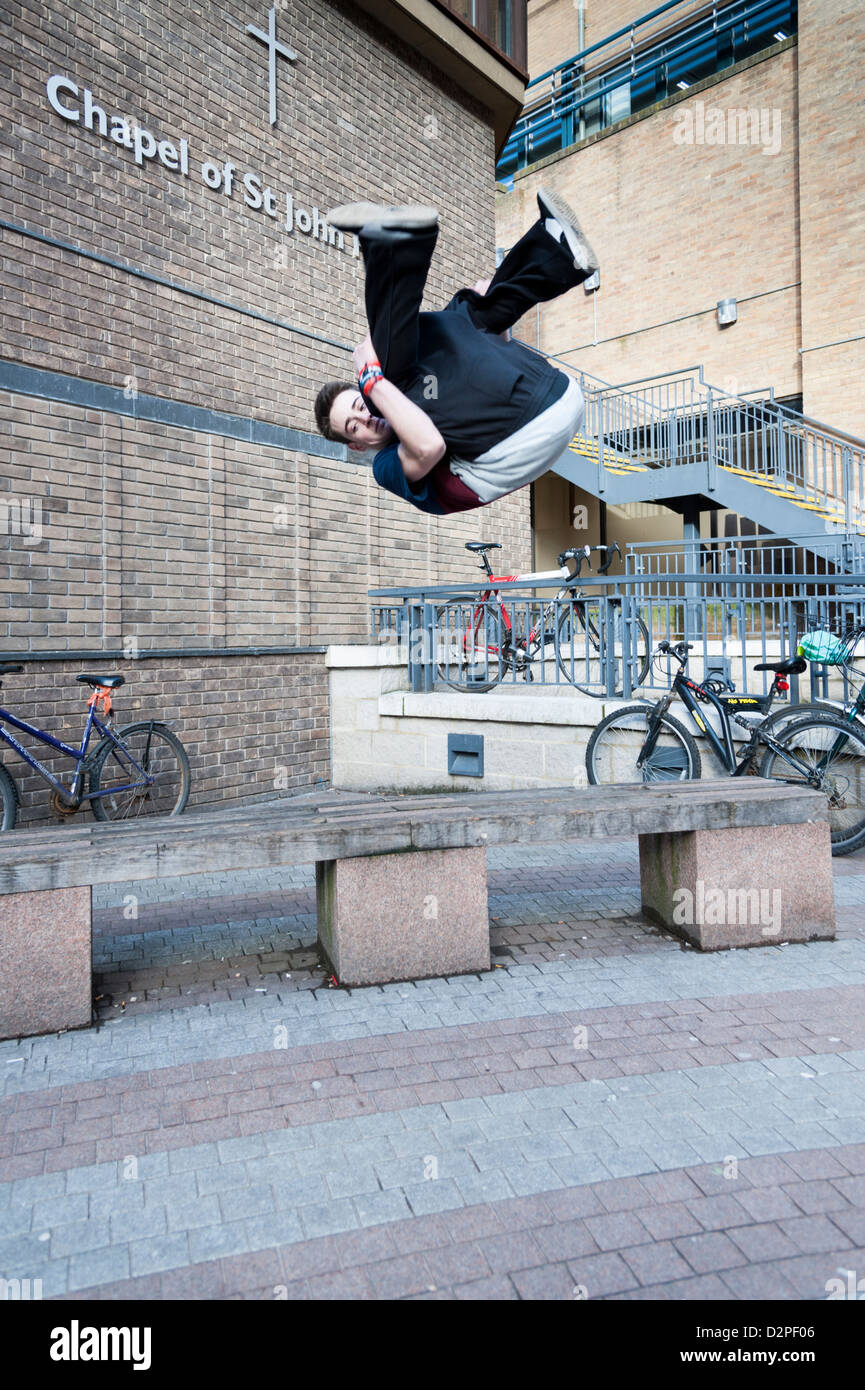 A young man free running or practicing parkour in Cambridge city centre using benches and walls to jump and climb - Stock Image