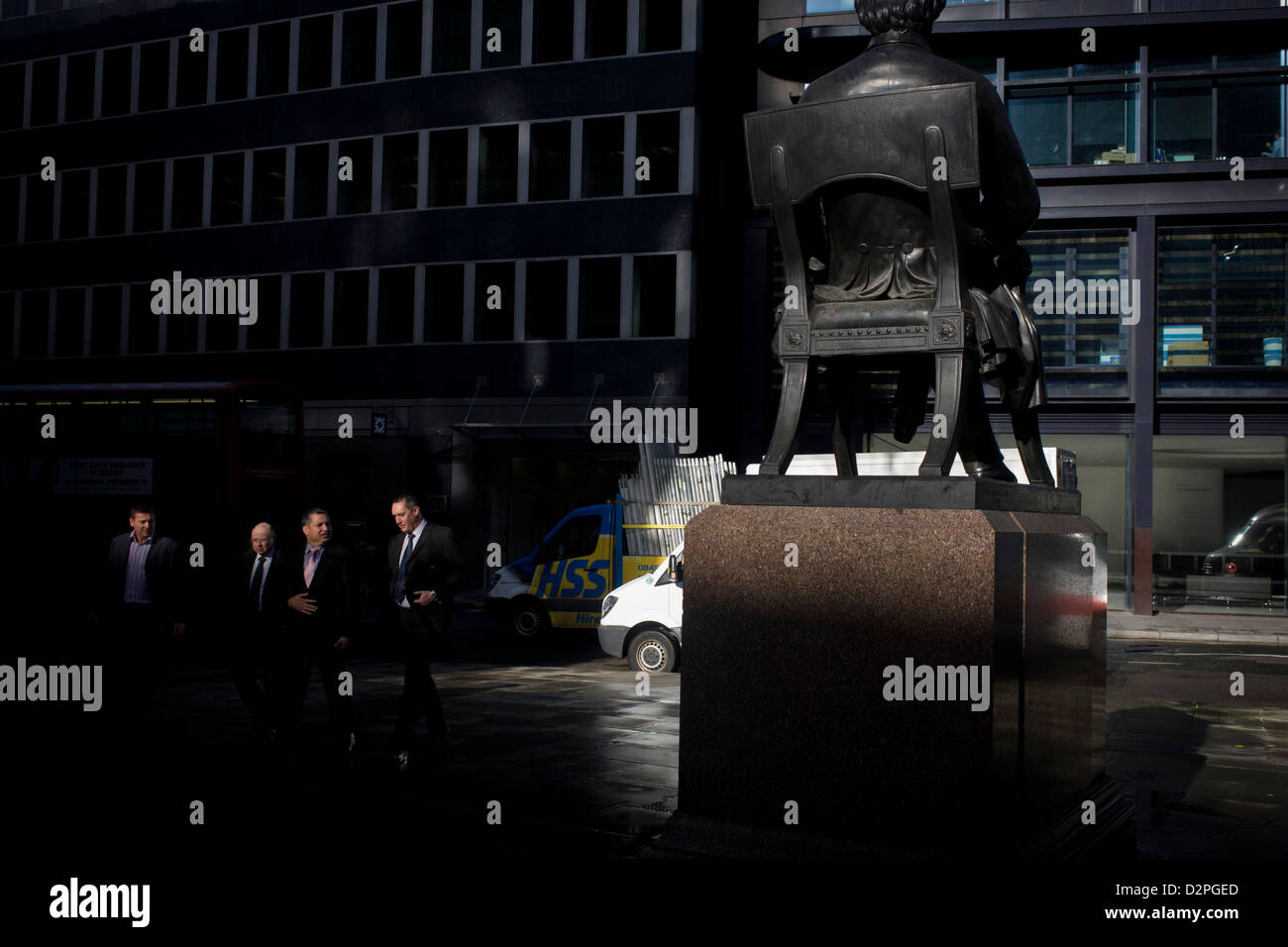 Businessmen walk past the statue of George Peabody in the heart of the financial City of London. Peabody was a philanthropist, - Stock Image