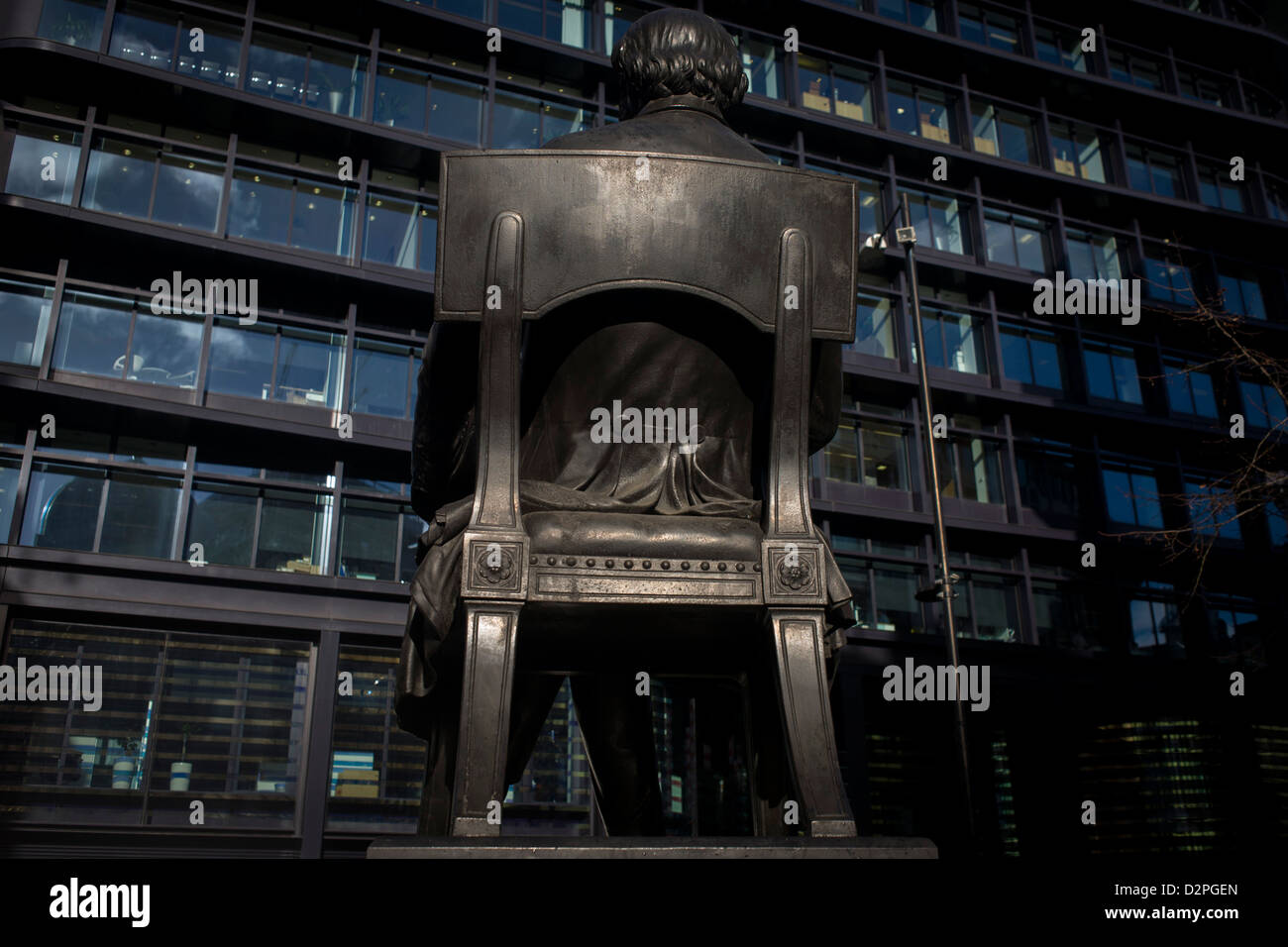 The rear of the statue of George Peabody and modern offices in the heart of the financial City of London. Peabody - Stock Image