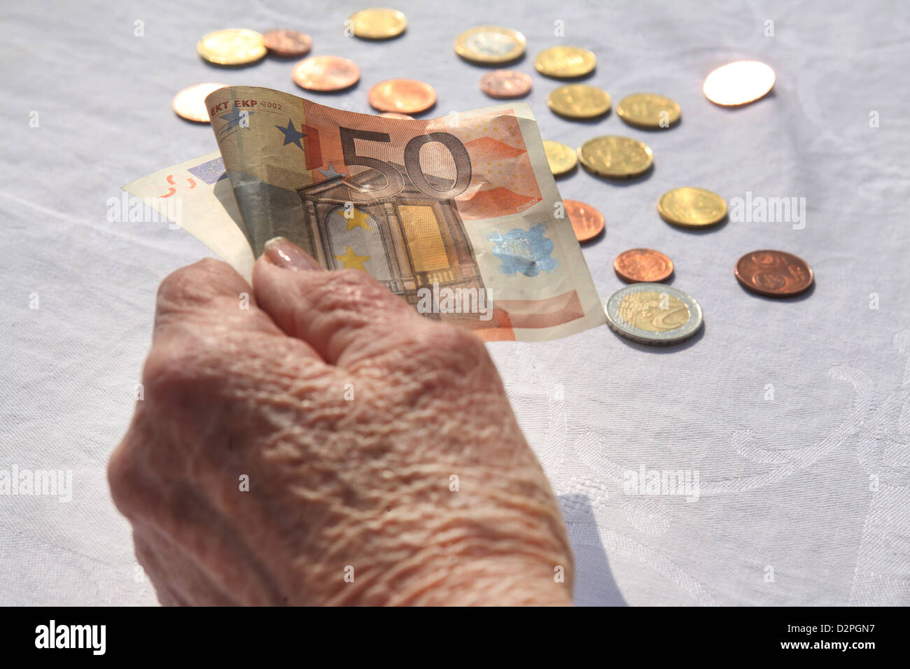 Berlin, Germany, the hand of a pensioner with a Euro note and coins - Stock Image