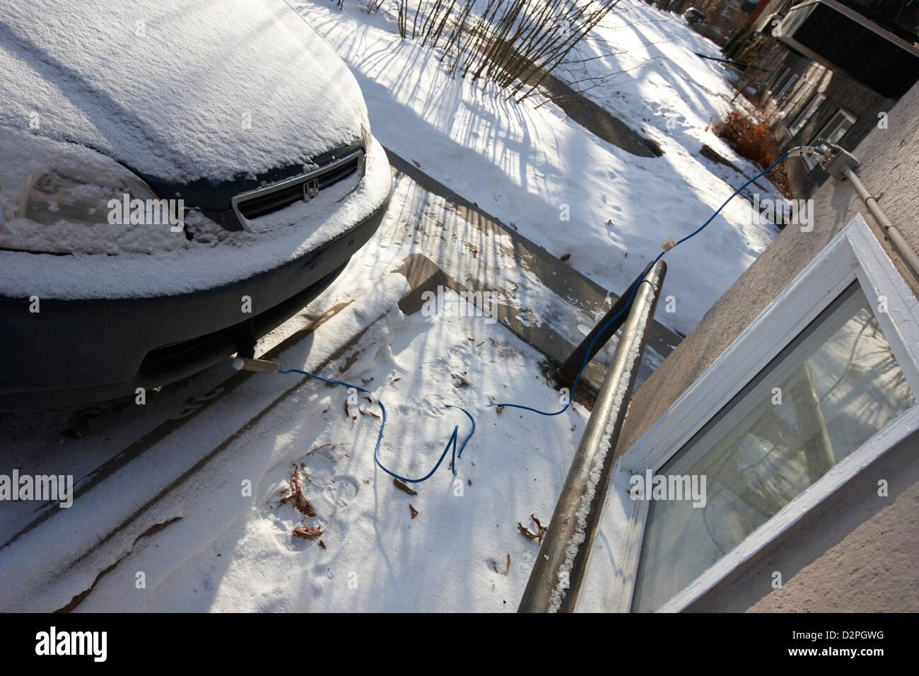 external power outlet connected to engine block heater of frozen car outside building in Saskatoon Saskatchewan - Stock Image