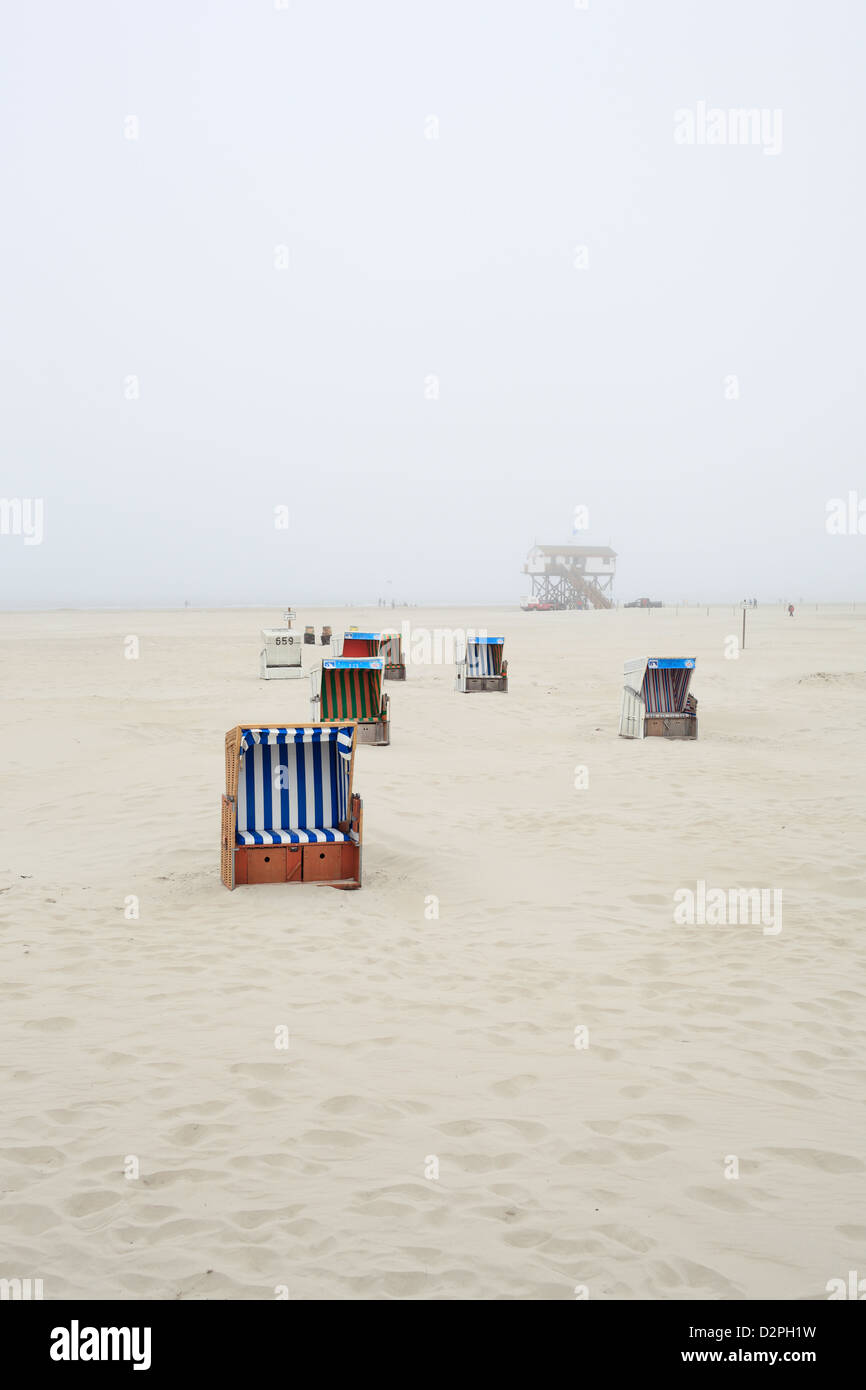 Sankt Peter-Ording, Germany, Strandkoerbe in fog at the beach - Stock Image