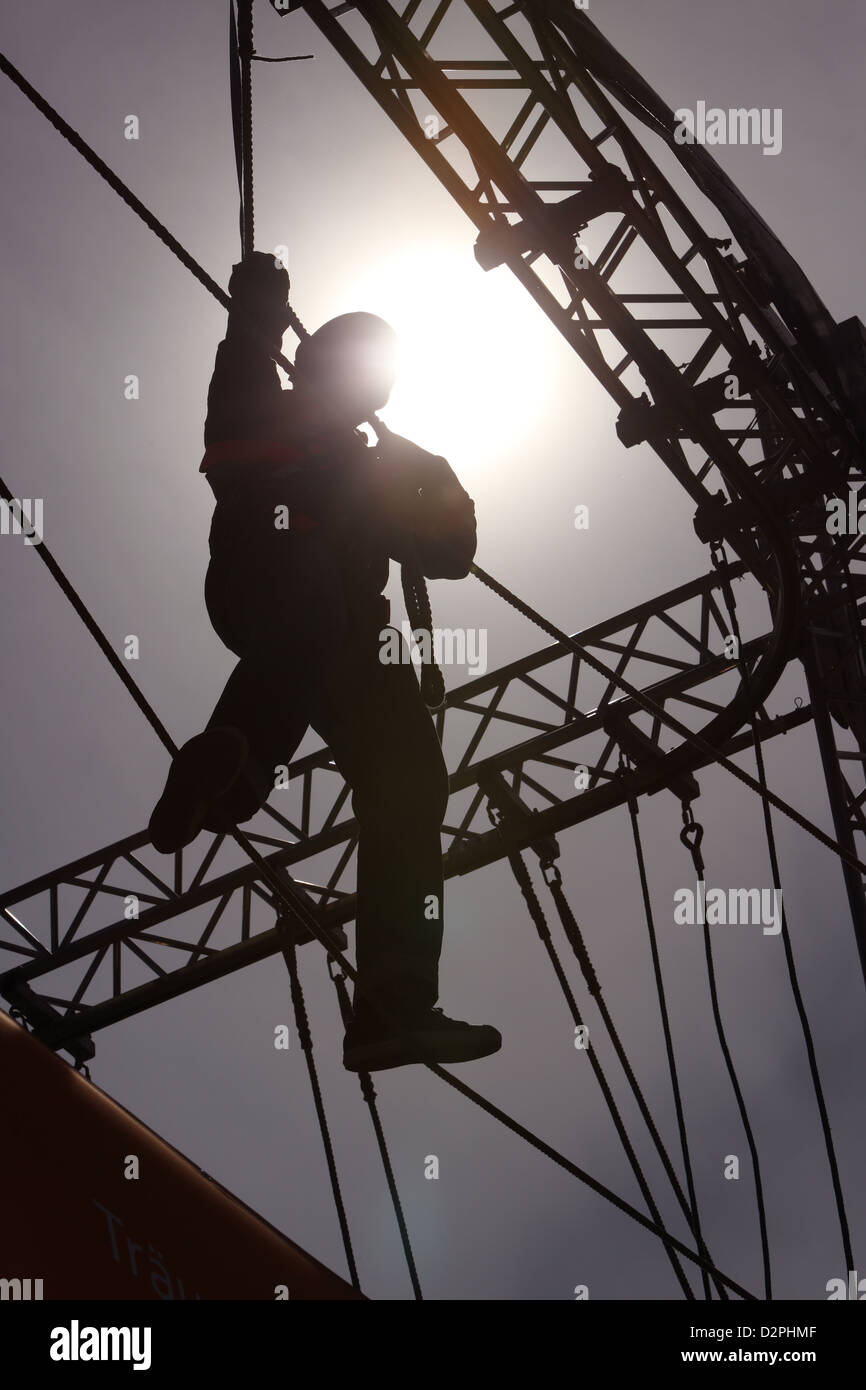 Berlin, Germany, silhouette, a person climbs into a high ropes course - Stock Image
