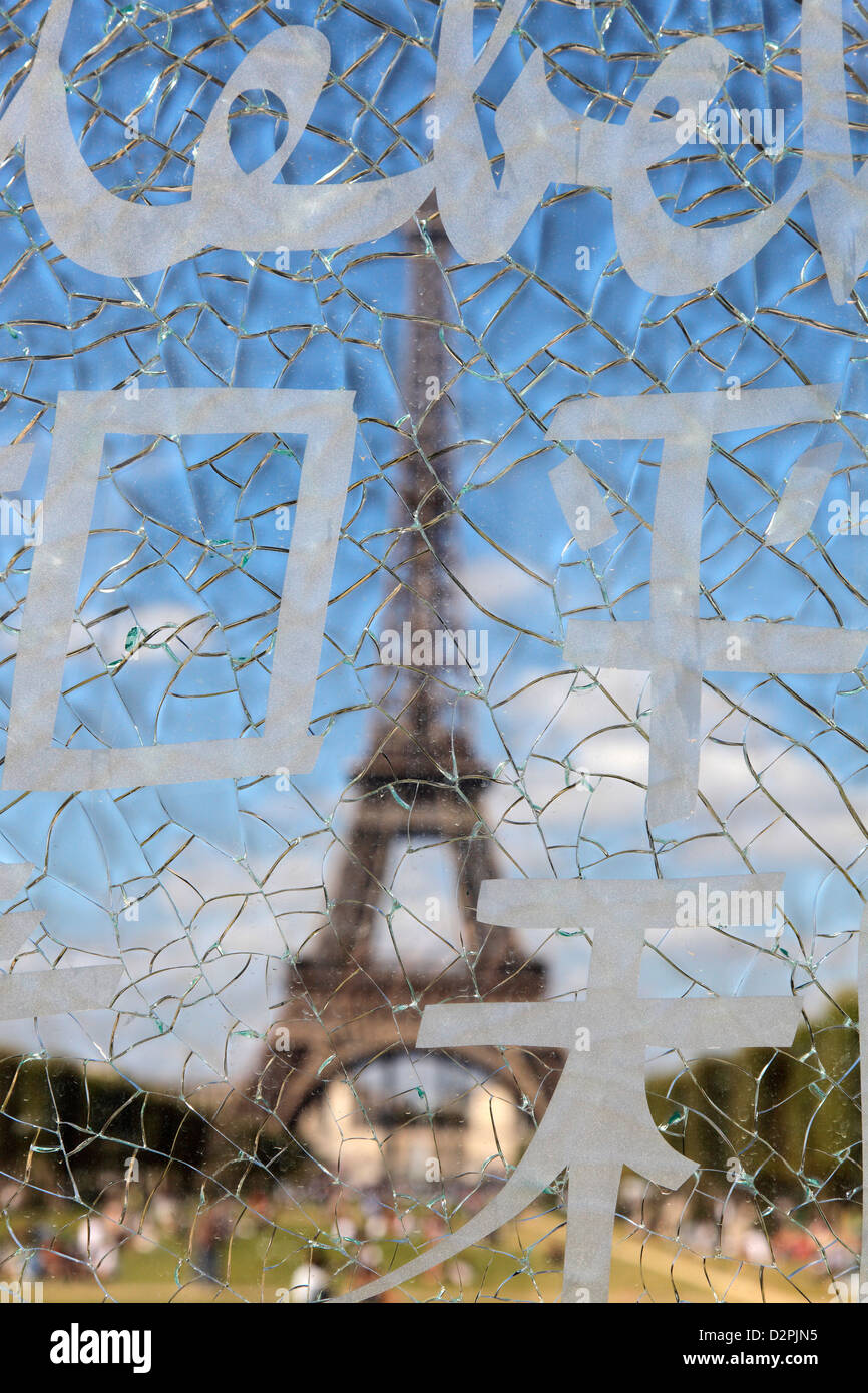 Eiffel Tower seen through the splintered pane of the wall of peace monument  at parc du