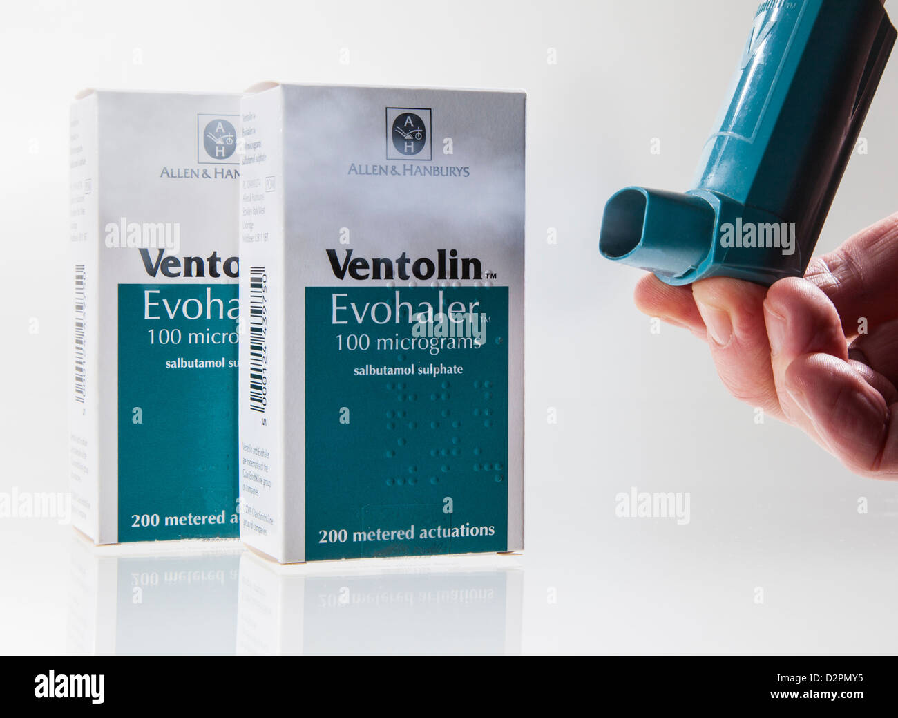 Ventolin asthma inhaler showing puff of medicine being dispensed and two boxes behind - Stock Image