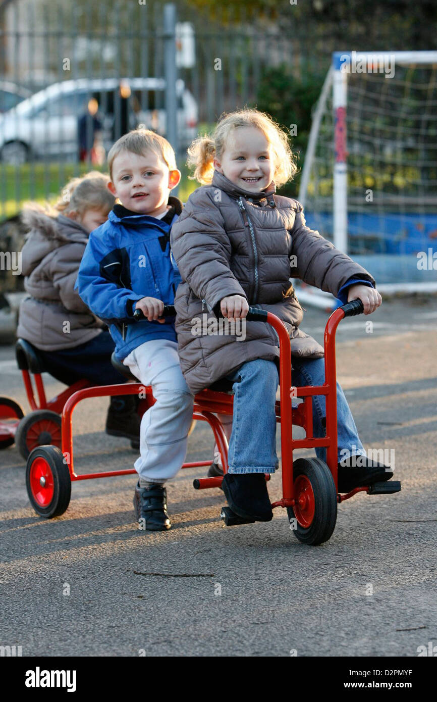 Young children playing on tricycles outdoors at a day nursery or playgroup. - Stock Image