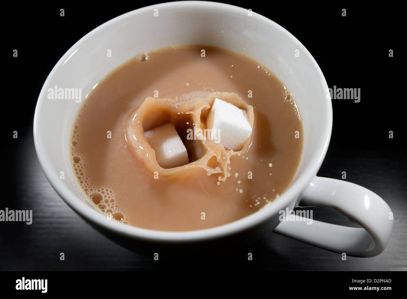 Lumps of white sugar being dropped into a hot cup of tea. - Stock Image
