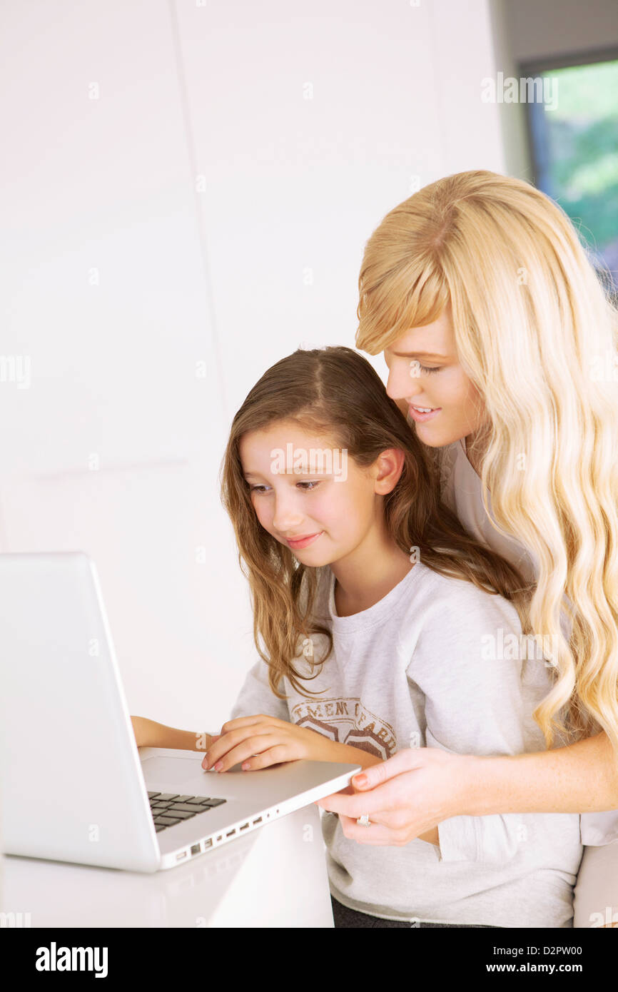 Mother and daughter working on laptop - Stock Image