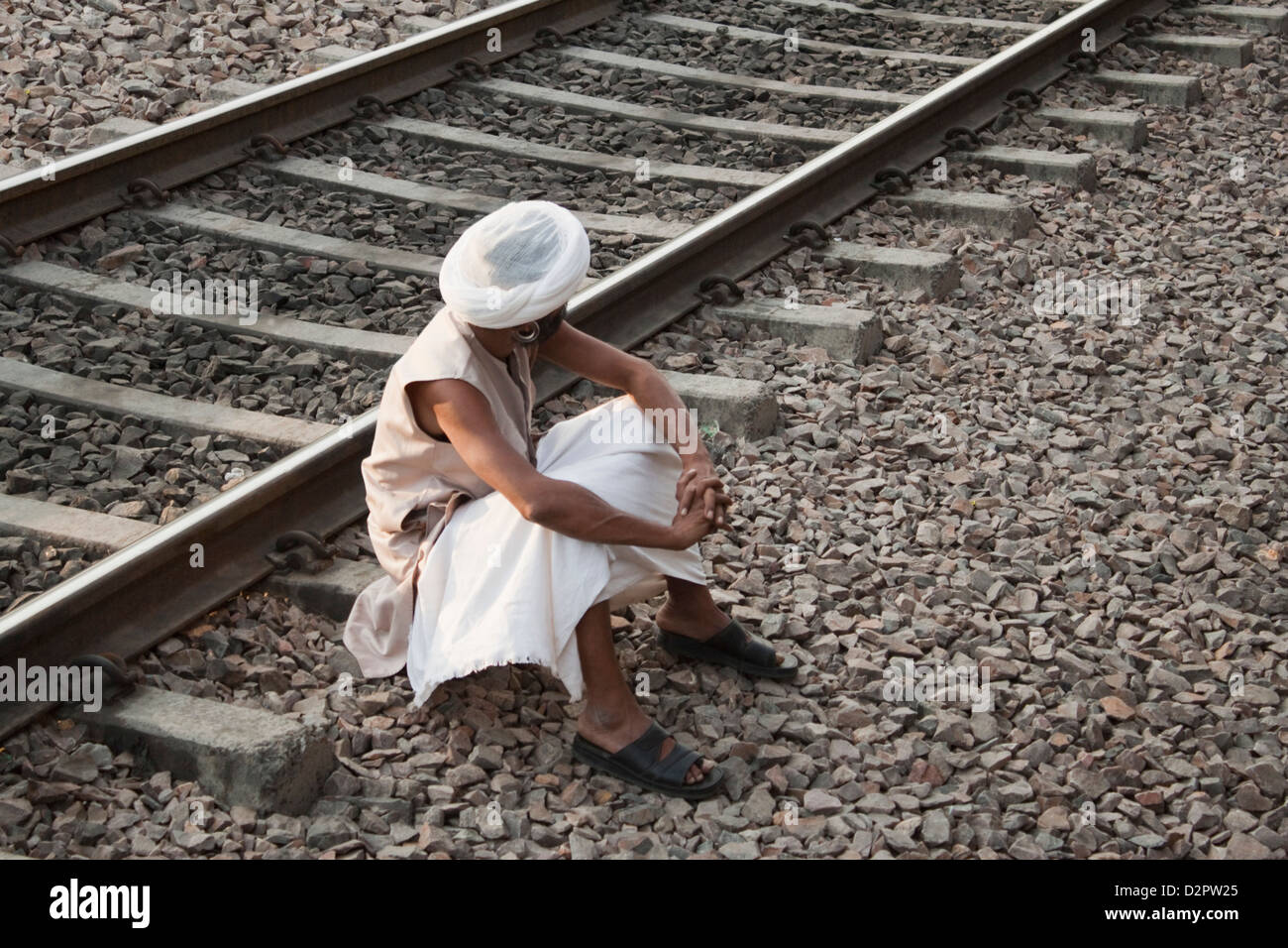 Man sitting near railroad track, Ahmedabad, Gujarat, India - Stock Image