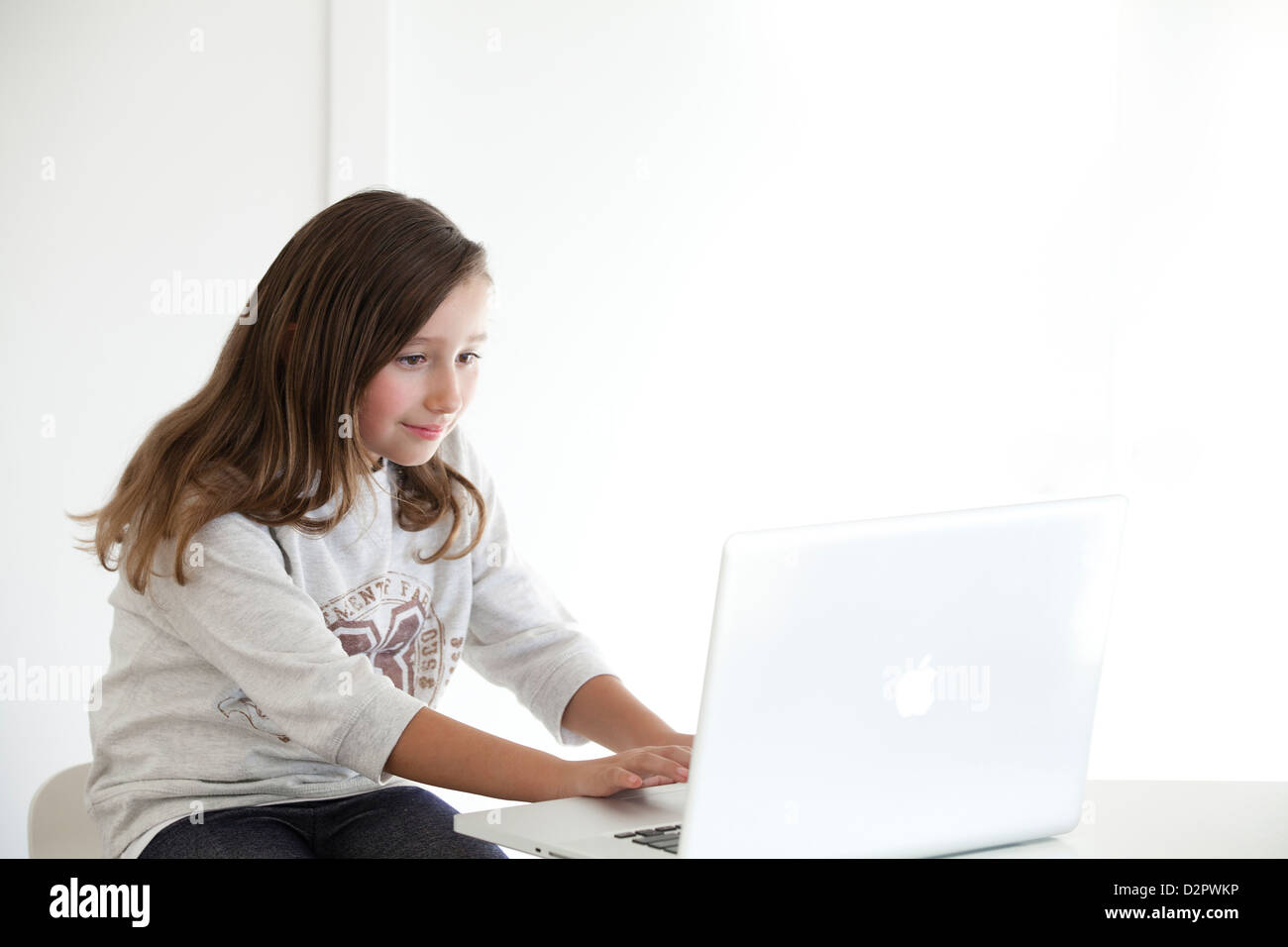 Young girl working on laptop - Stock Image