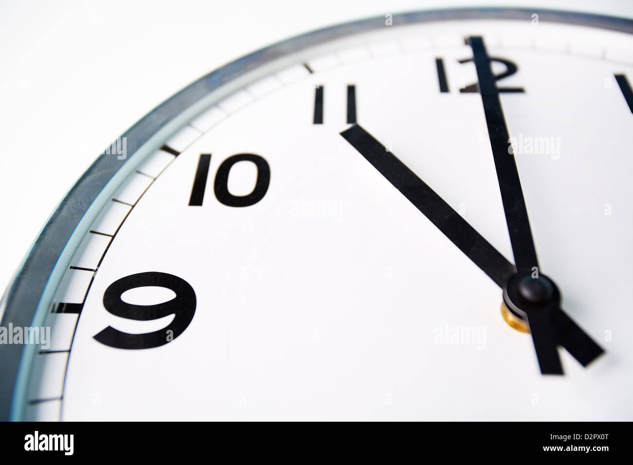 Macro shot of a clock face showing eleven o'clock - Stock Image