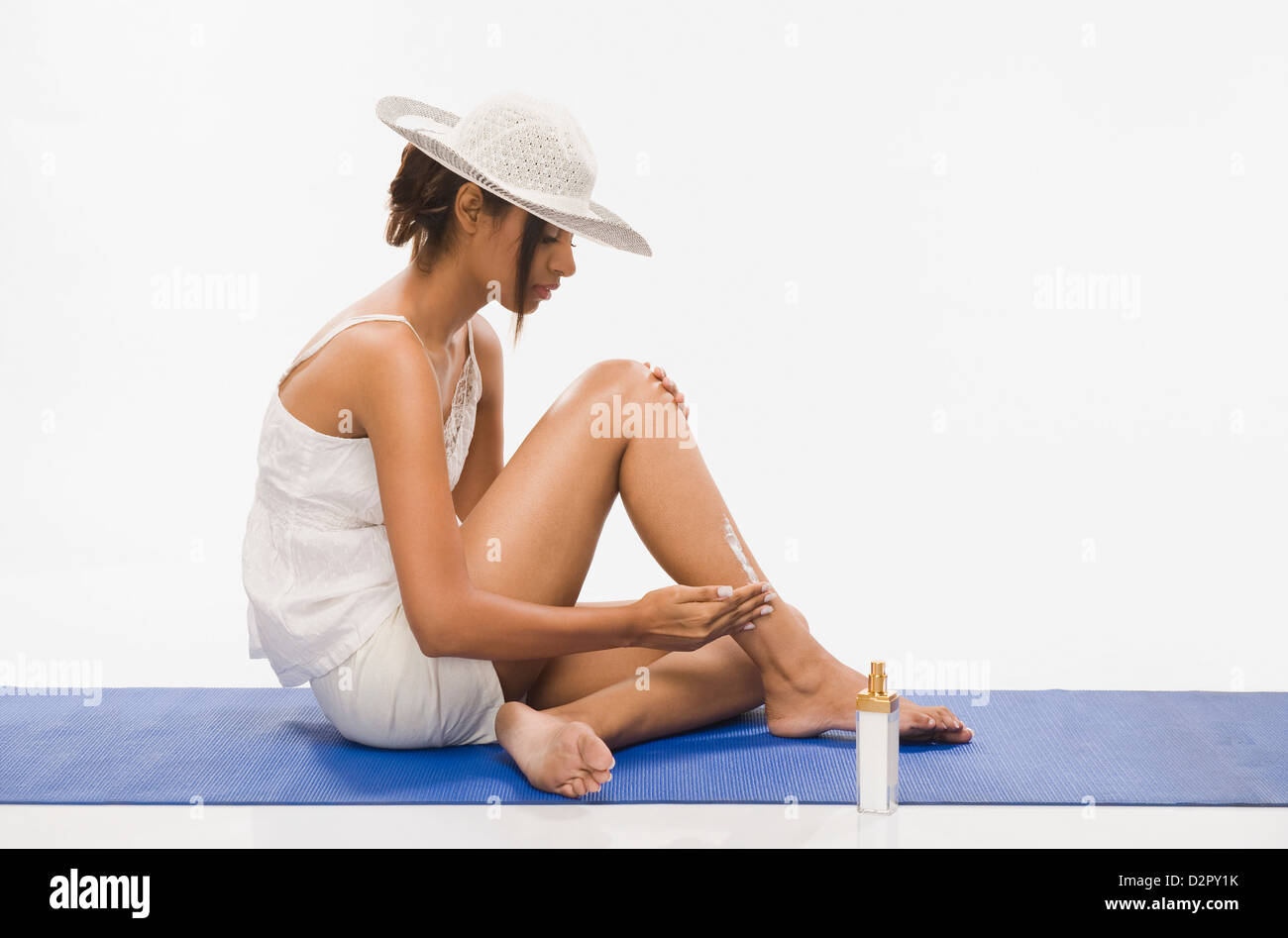 Woman applying suntan lotion - Stock Image