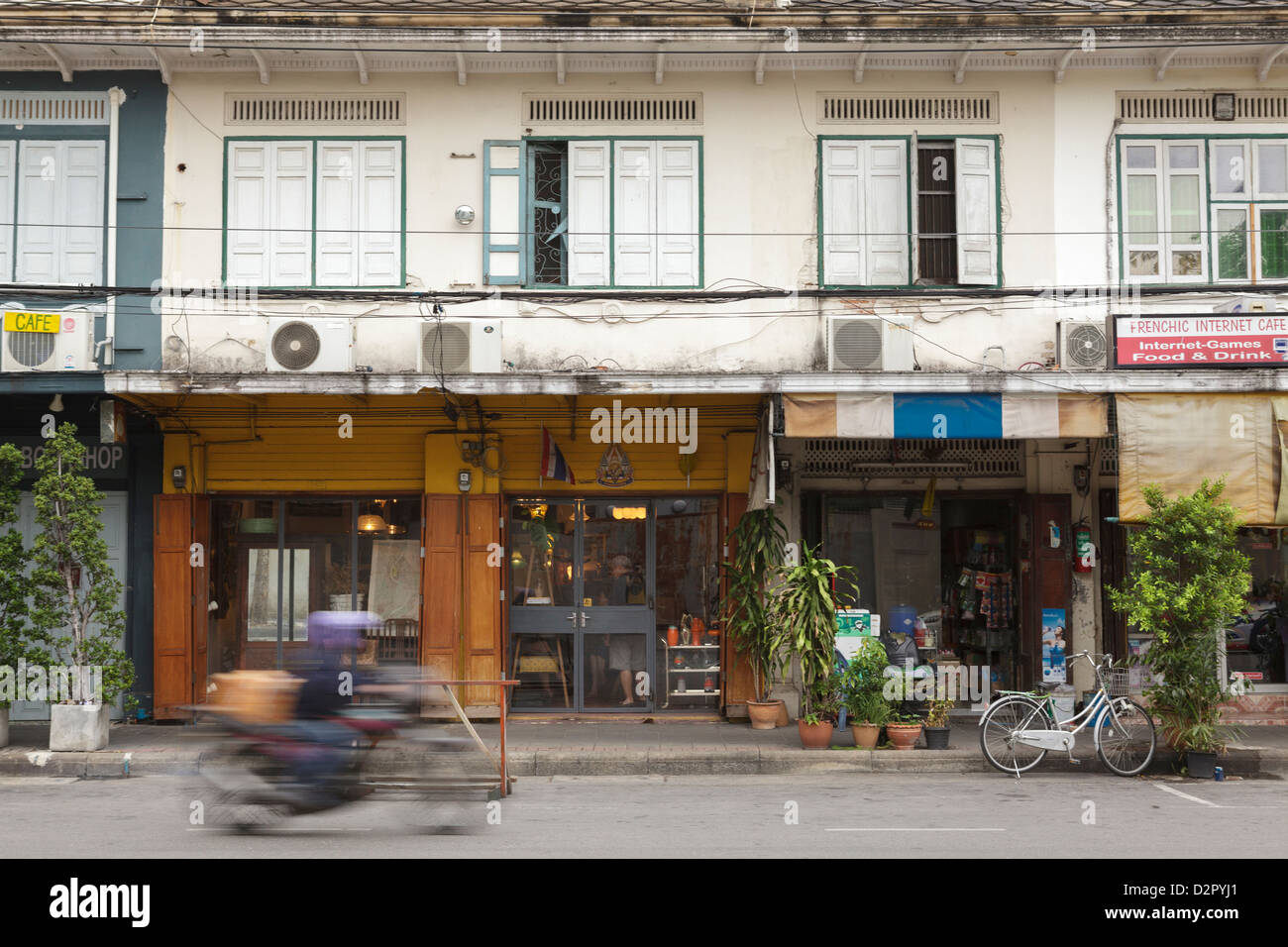 A motorbike rides past a shop front in Rattanakosin, Bangkok, Thailand, Southeast Asia, Asia - Stock Image