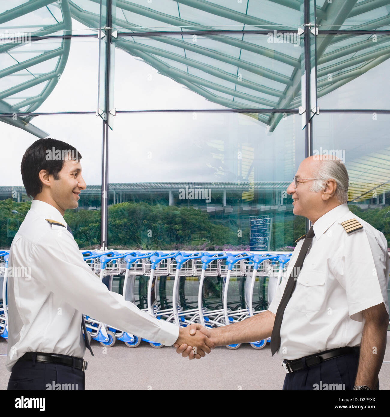 Two pilots shaking hands and smiling - Stock Image