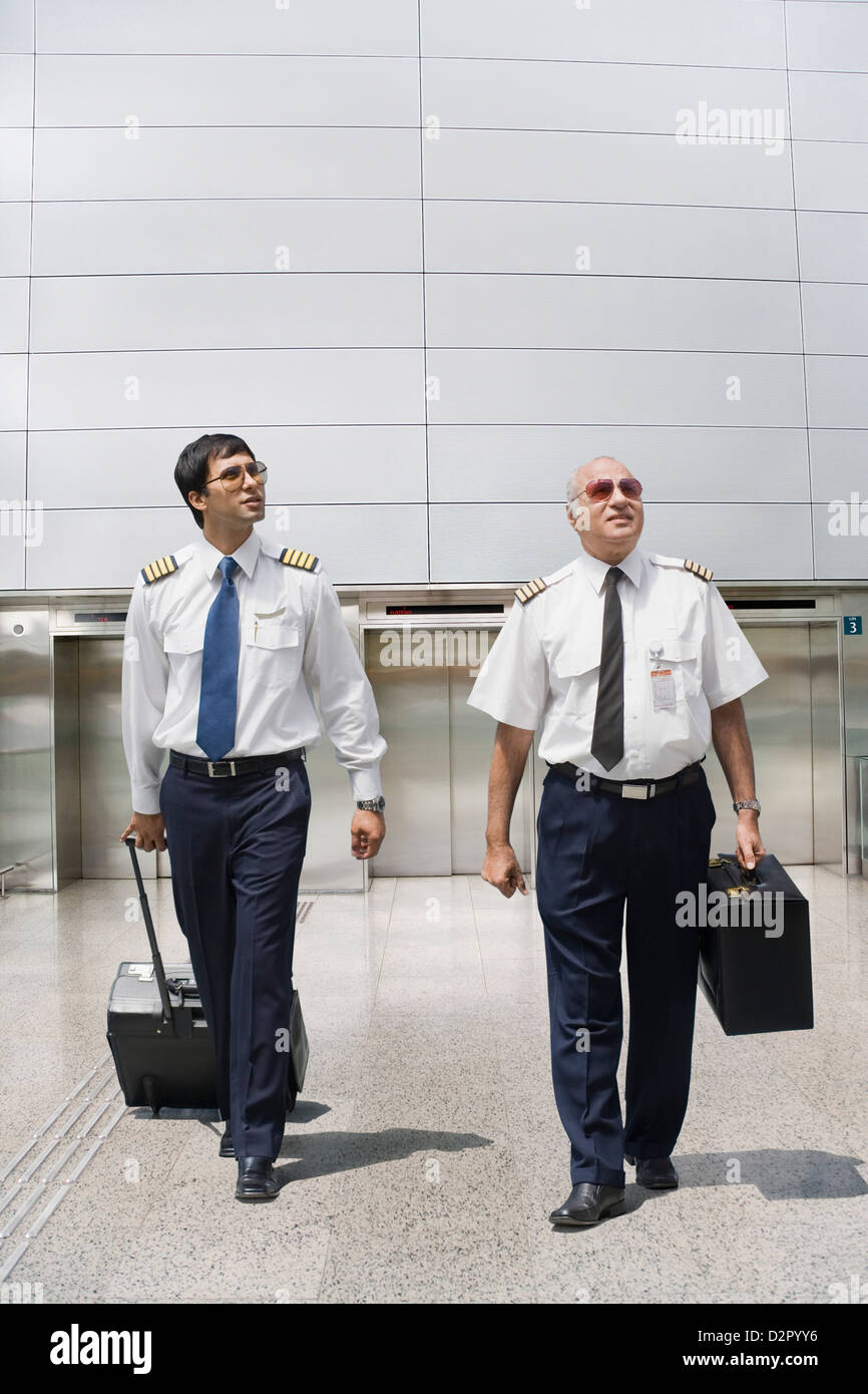 Two pilots carrying their luggage at an airport - Stock Image