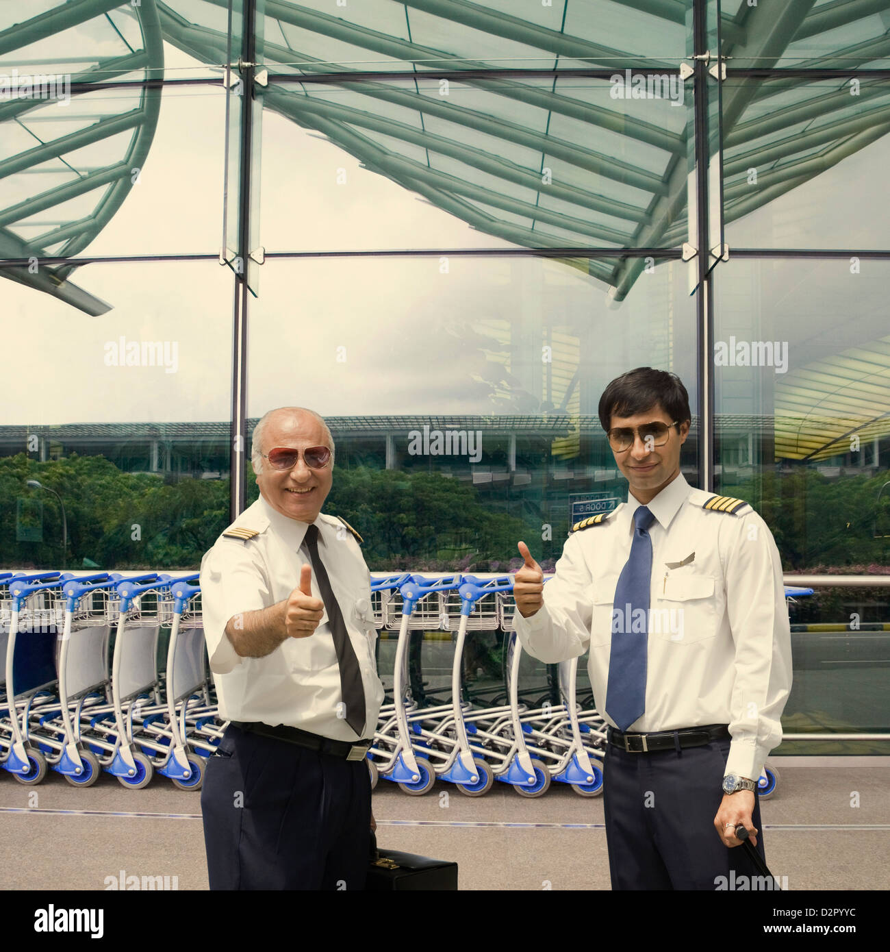 Two pilots showing thumbs up at an airport - Stock Image