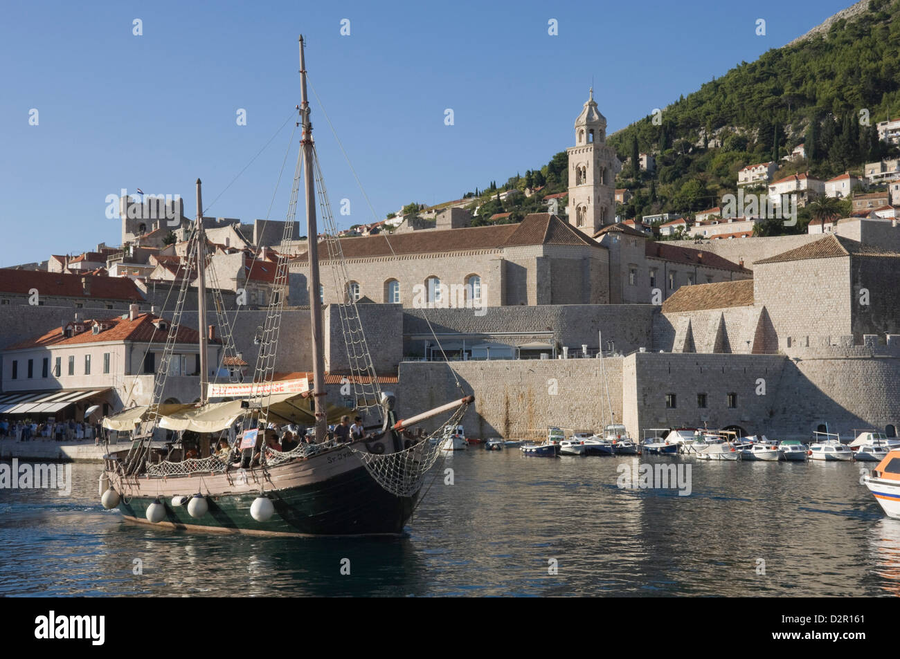Tourist boat in the old harbour with the bell tower of the Franciscan Monastery in the background, Old Town, Dubrovnik, - Stock Image