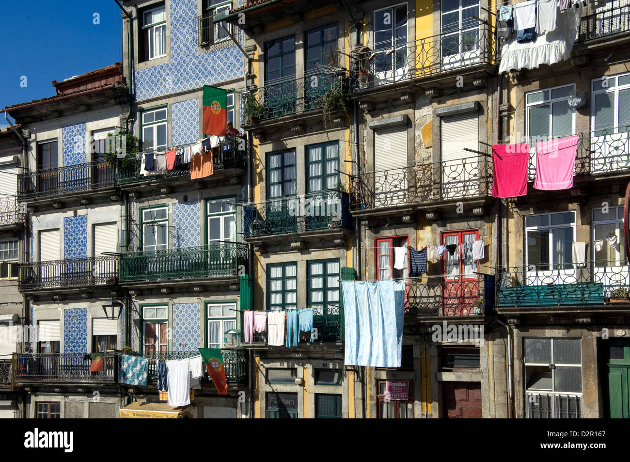 A street in the old town with traditional balconies, tiled panels on the outside walls, washing hanging, Oporto, - Stock Image