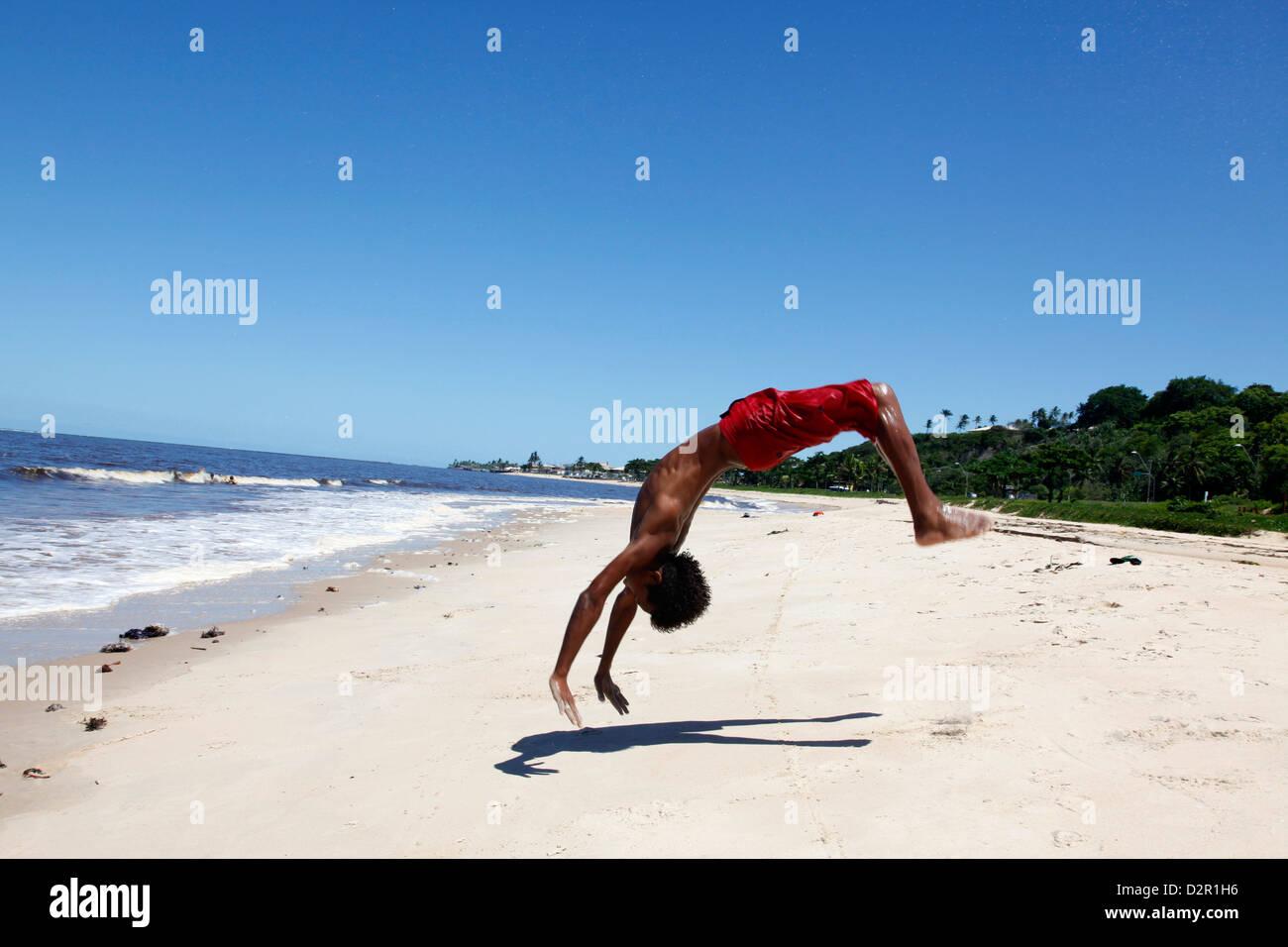 Young man doing acrobatics on Rio da Vila beach, Porto Seguro, Bahia, Brazil, South America - Stock Image