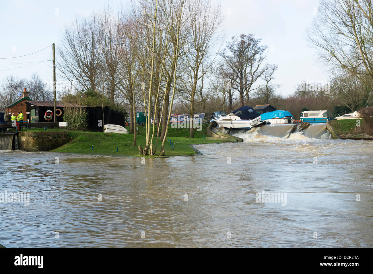 Little Baddow, Essex, UK. 31st January 2013.  A motor cruiser, Miss Behavin', sits precariously on a weir at Paper Stock Photo