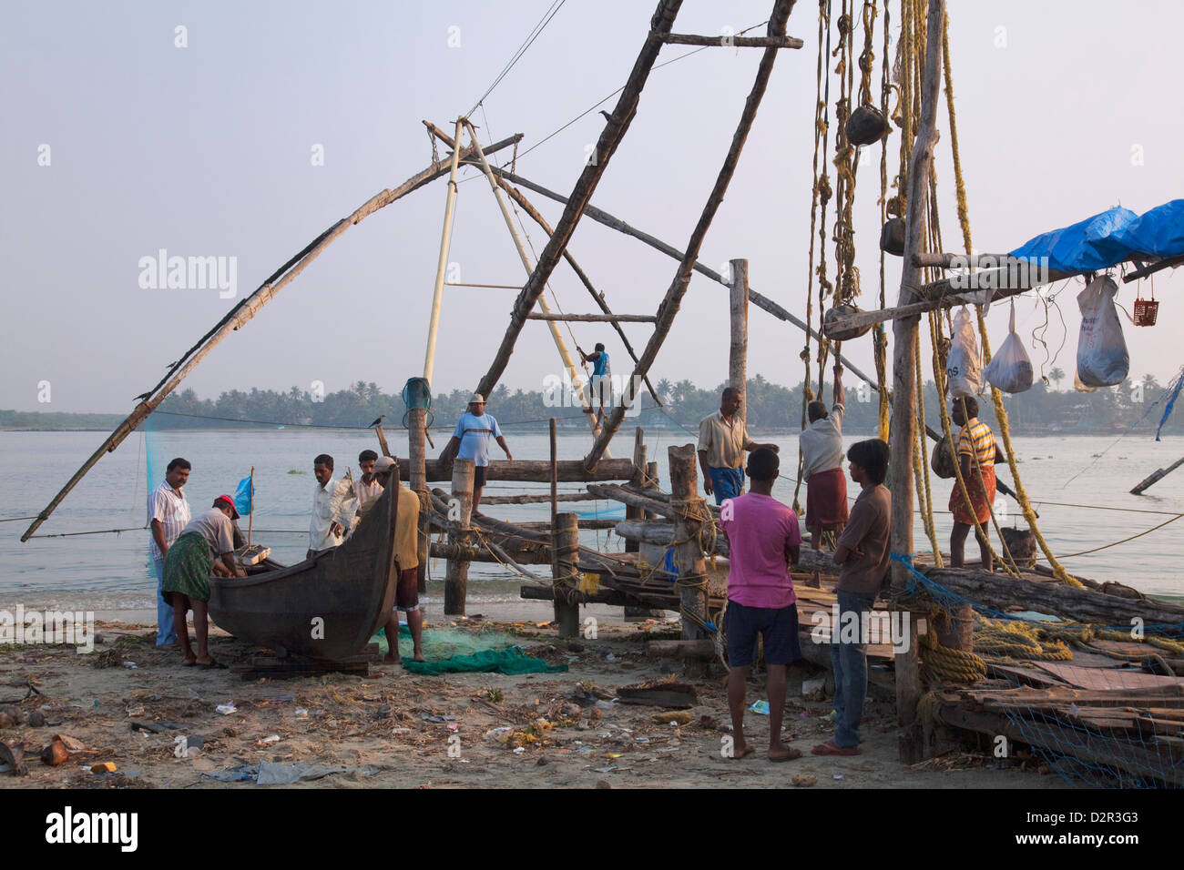 Fishermen preparing traditional boat and Chinese fishing net on the waterfront at Kochi (Cochin), Kerala, India, - Stock Image