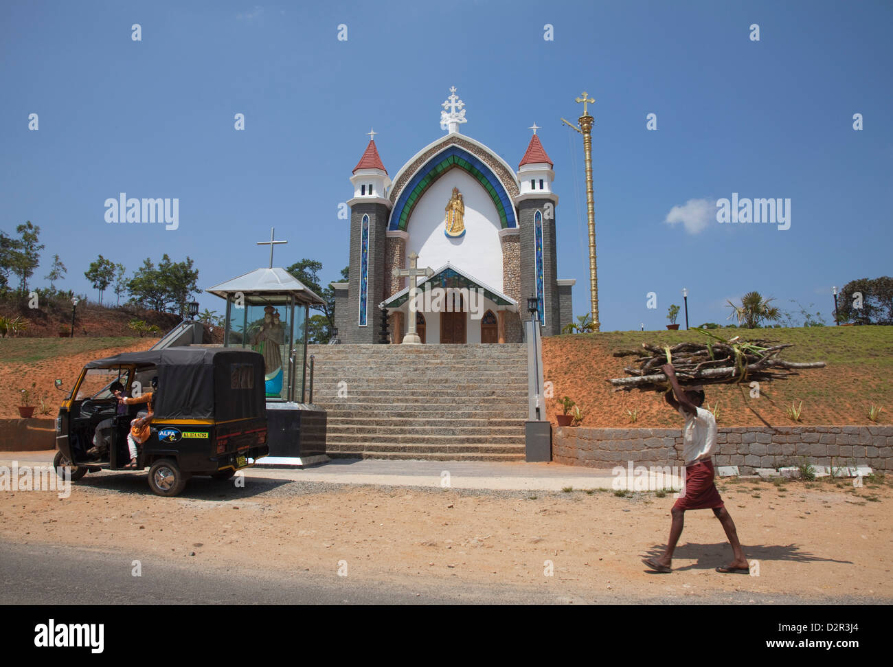 Man carrying firewood on his head walking past a church in rural Kerala, India, Asia Stock Photo