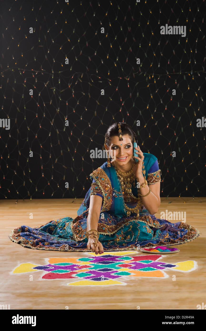 Woman talking on a mobile phone and making rangoli Stock Photo