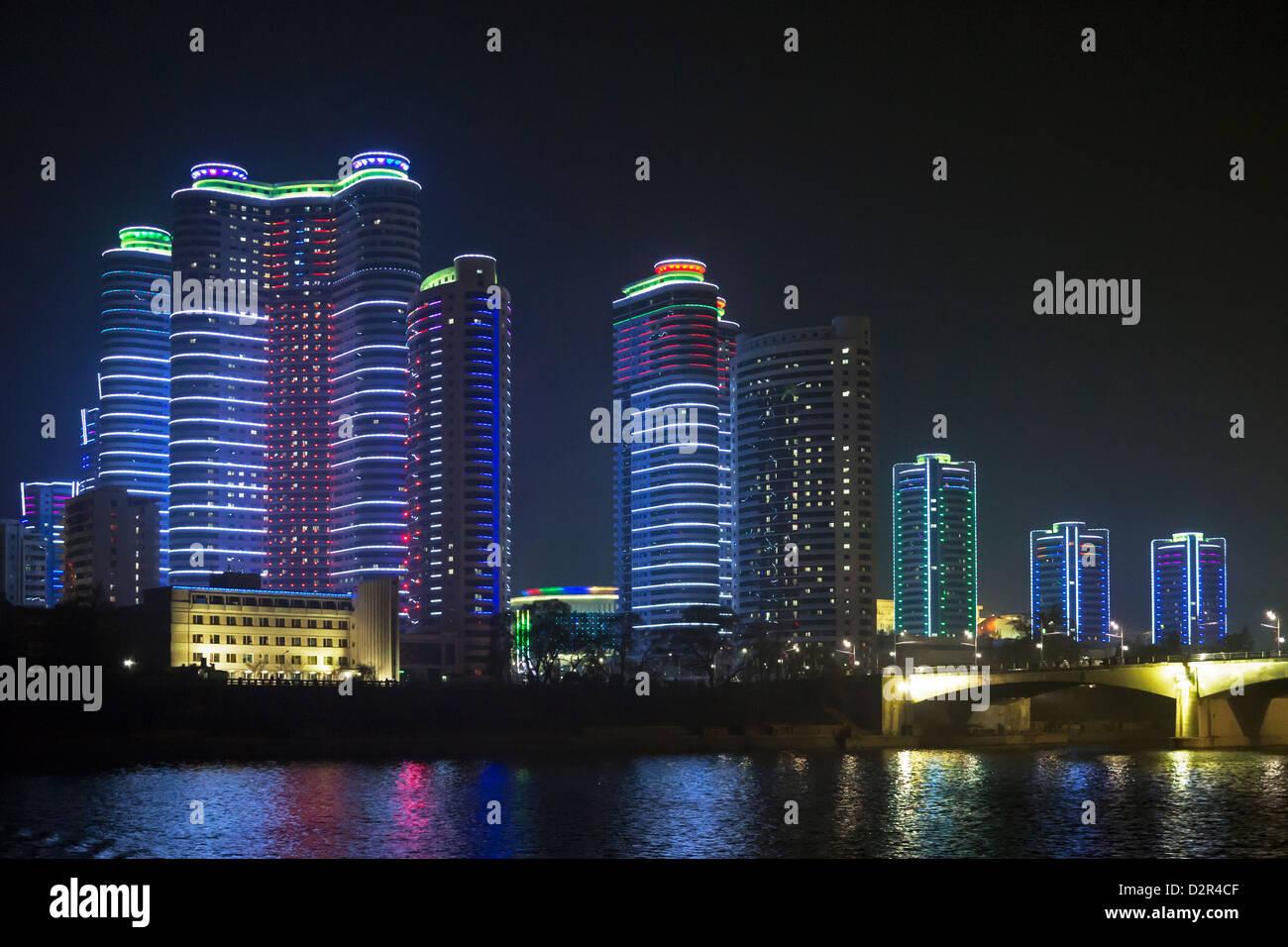 Modern city apartments illuminated at night, Pyongyang, Democratic People's Republic of Korea (DPRK), North - Stock Image