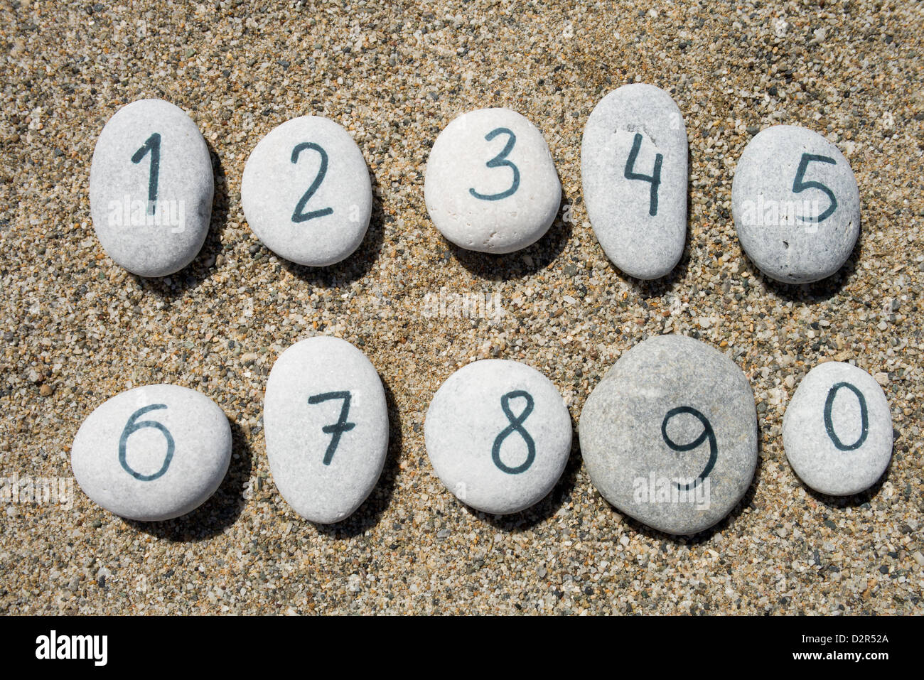 0 to 9 digits on group of stones with sand background - Stock Image
