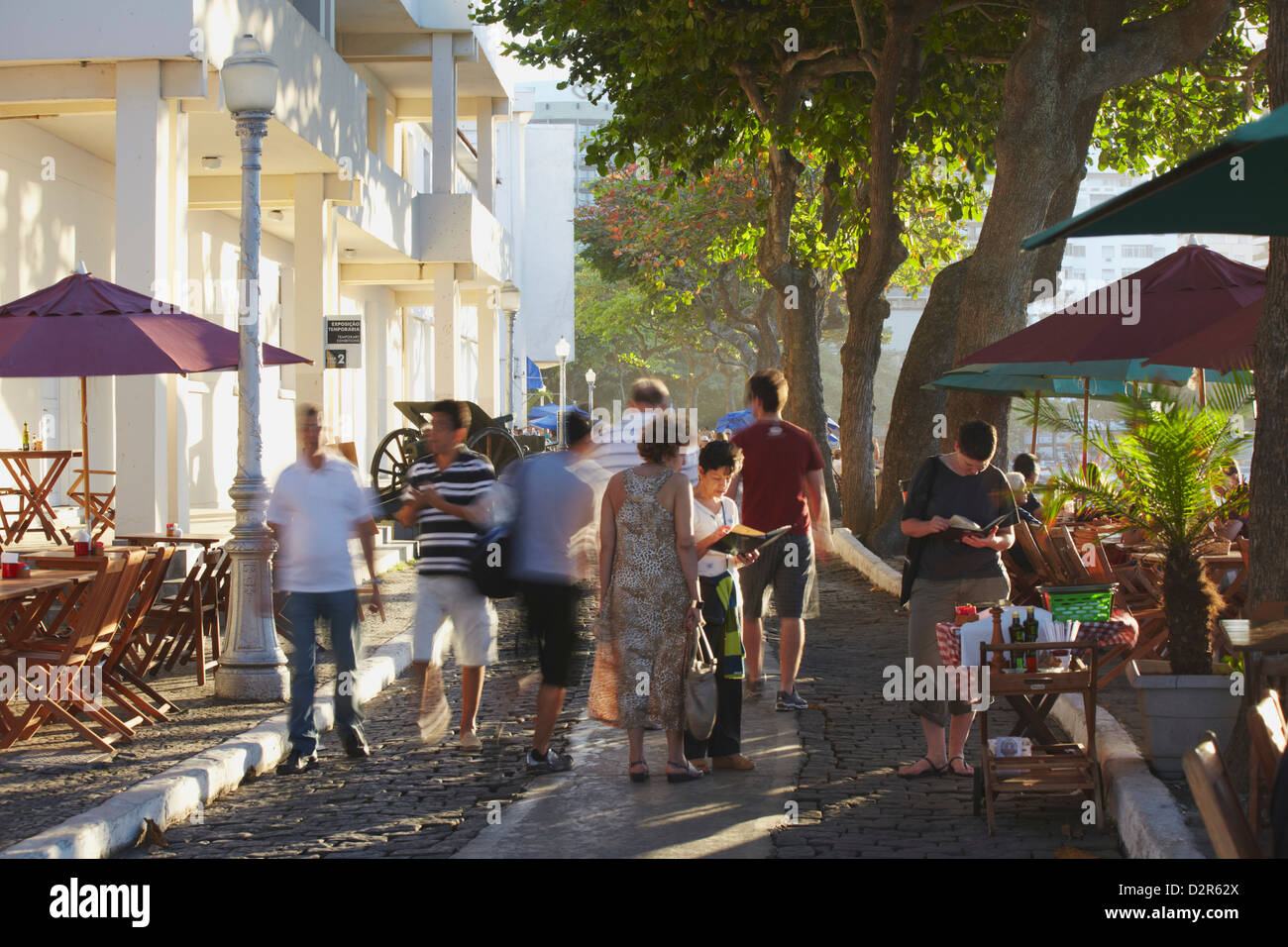 People walking past cafes in the grounds of Forte de Copacabana (Copacabana Fort), Copacabana, Rio de Janeiro, Brazil - Stock Image