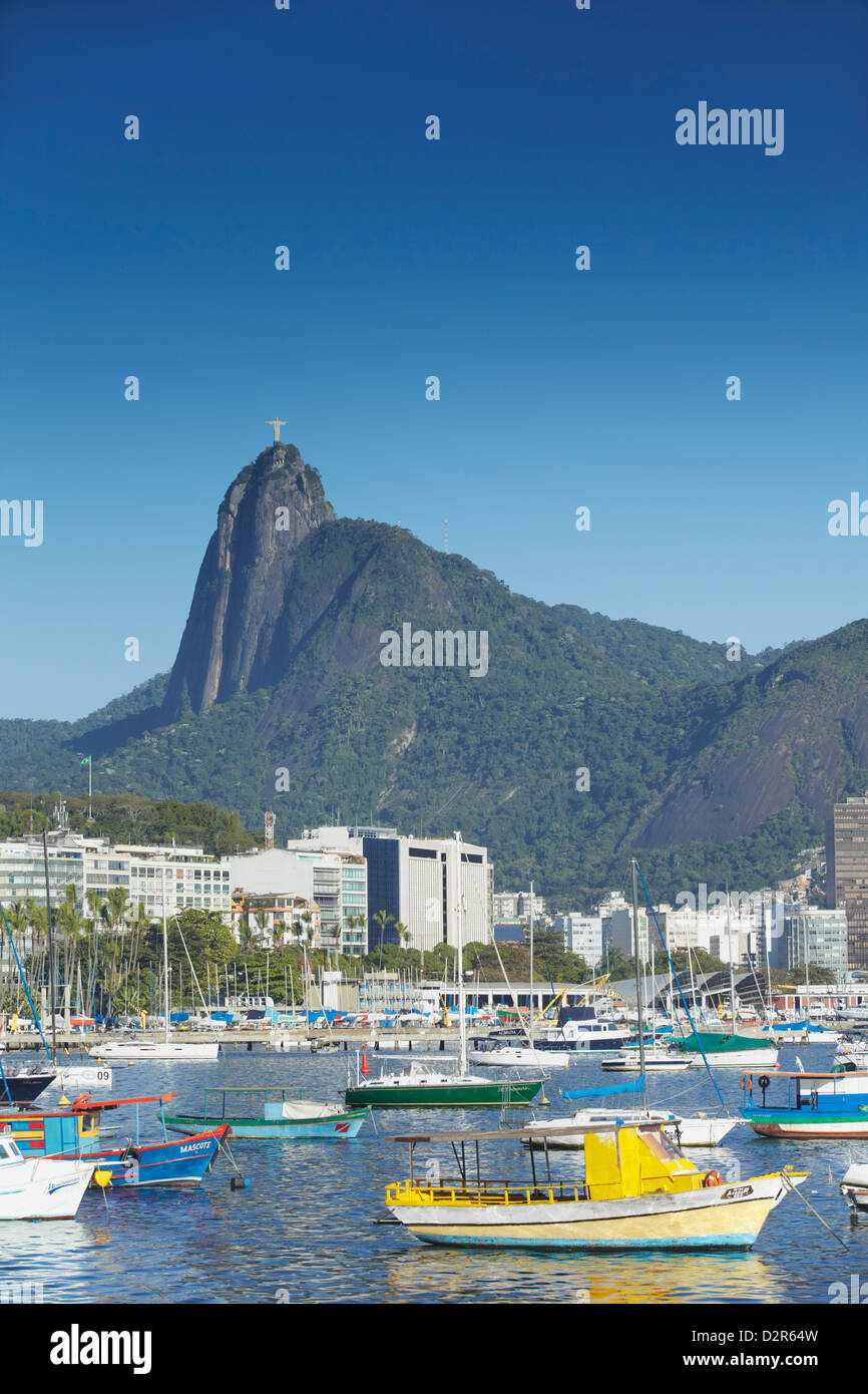 Boats moored in harbour with Christ the Redeemer statue in background, Urca, Rio de Janeiro, Brazil, South America Stock Photo