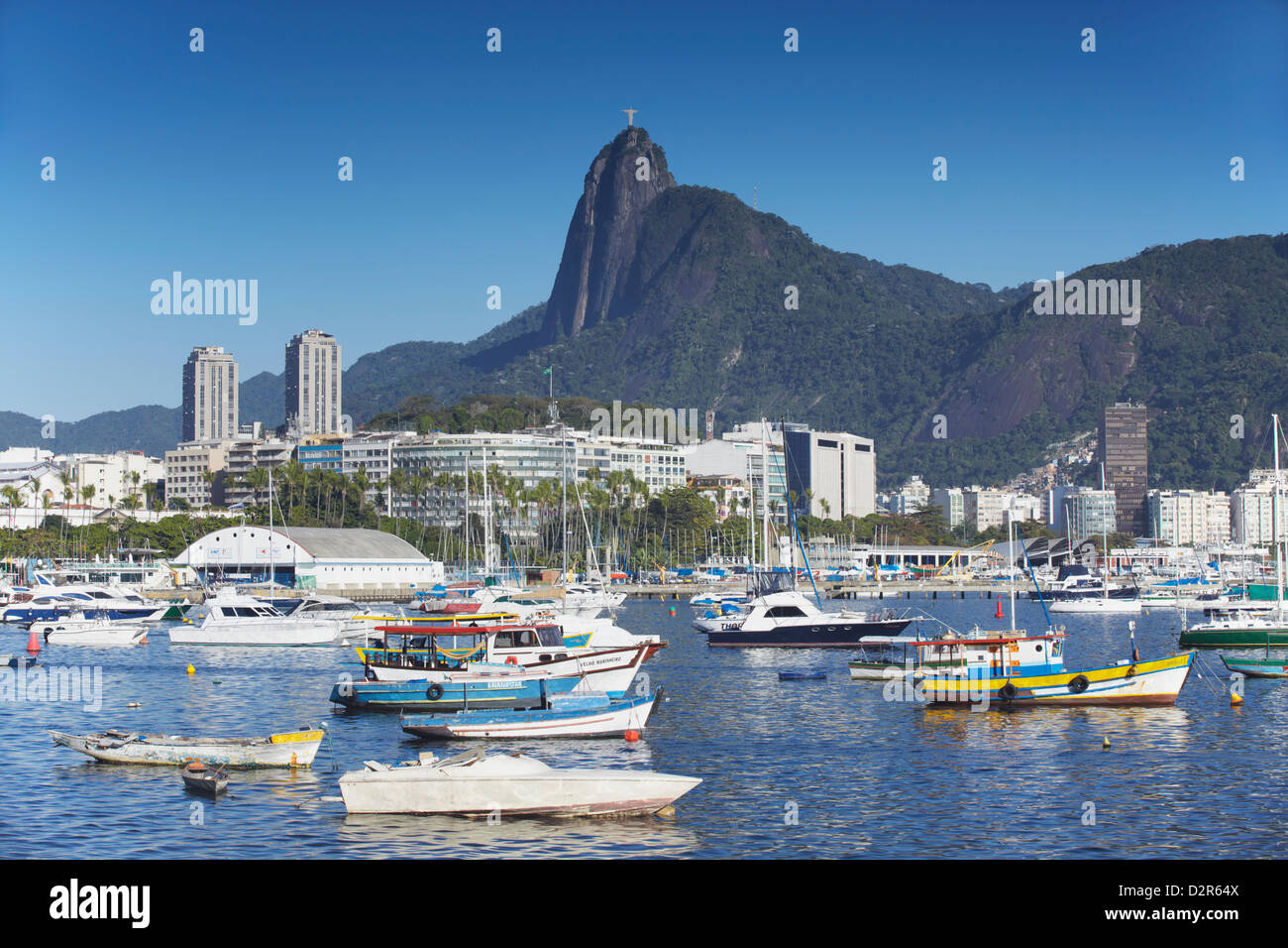 Boats moored in harbour with Christ the Redeemer statue in background, Urca, Rio de Janeiro, Brazil, South America - Stock Image