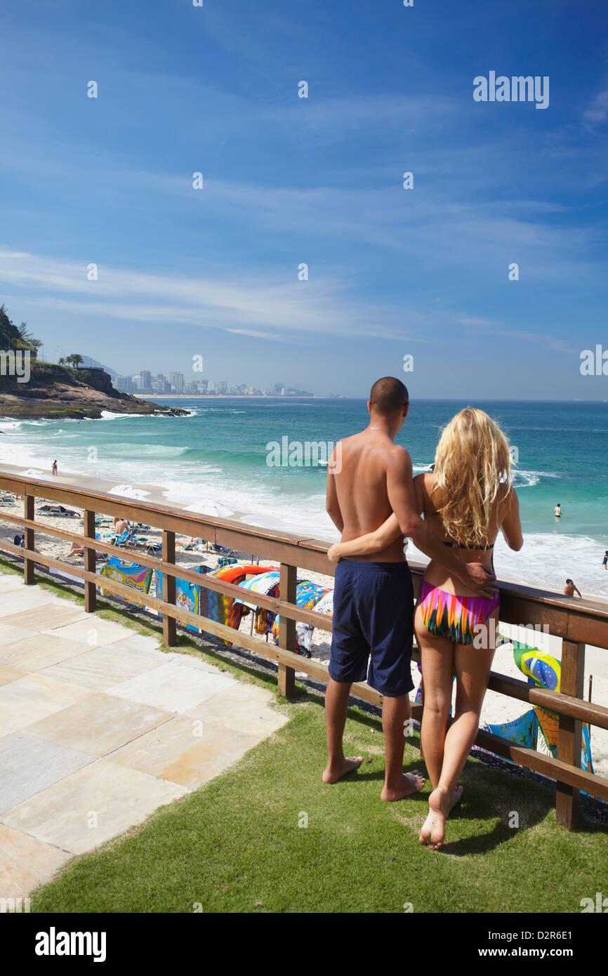 Couple standing in grounds of Sheraton Hotel overlooking beach, Rio de Janeiro, Brazil, South America - Stock Image