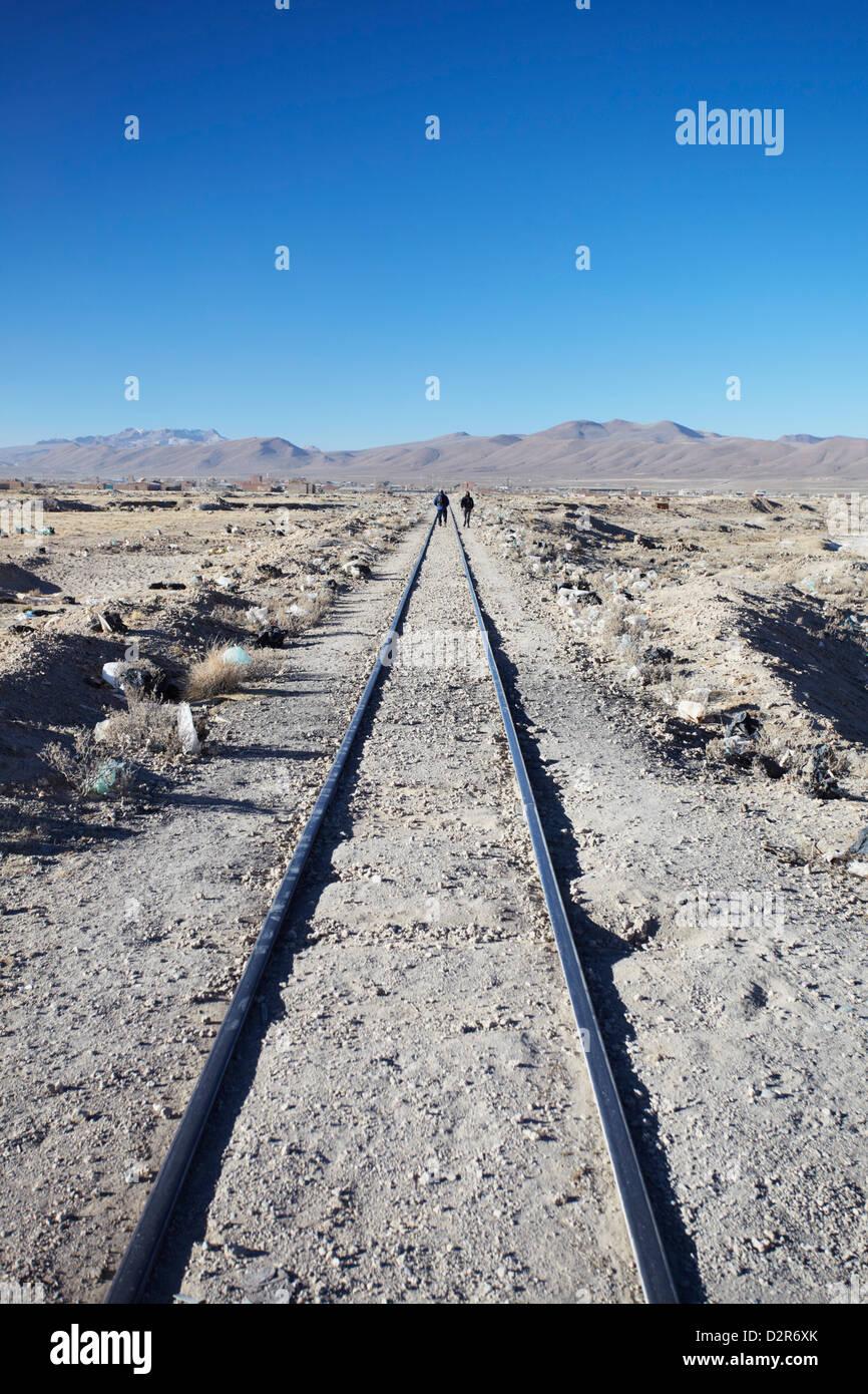 People walking along train tracks, Uyuni, Potosi Department, Bolivia, South America - Stock Image