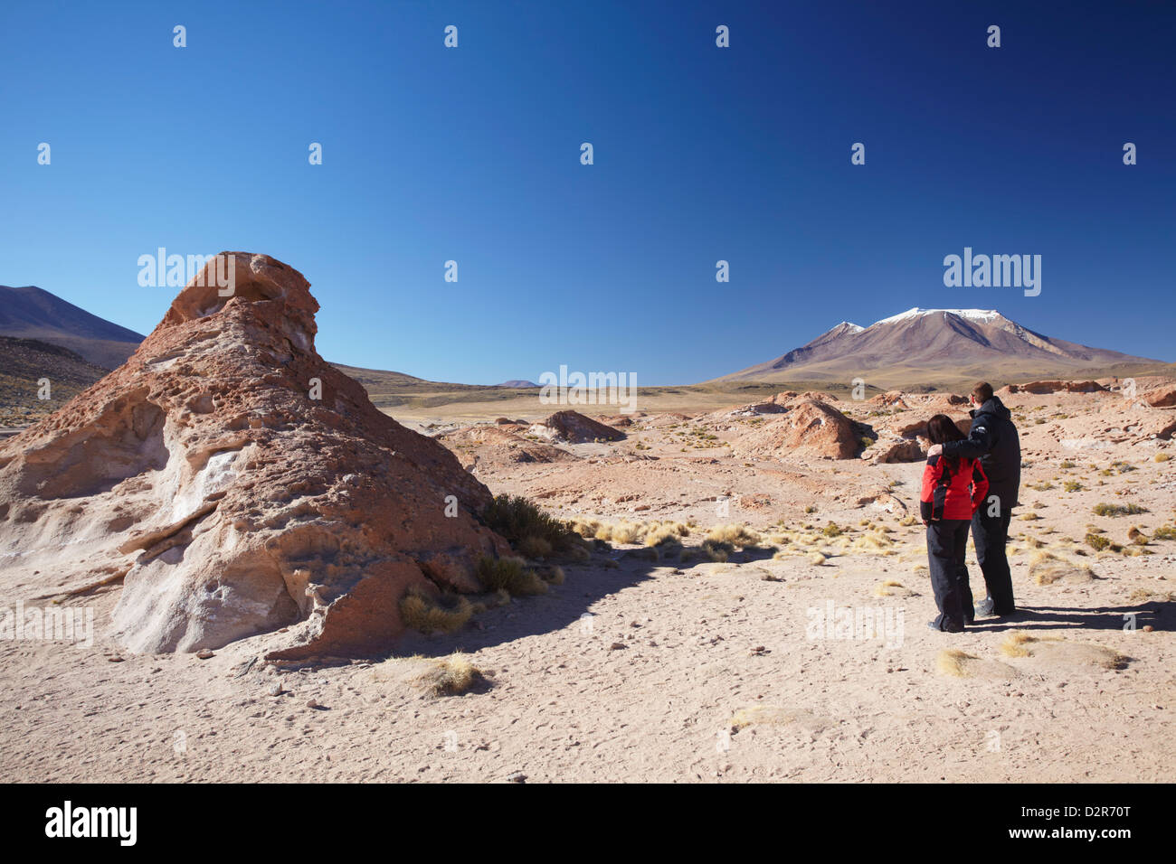 Couple looking at volcano on Altiplano, Potosi Department, Bolivia, South America - Stock Image