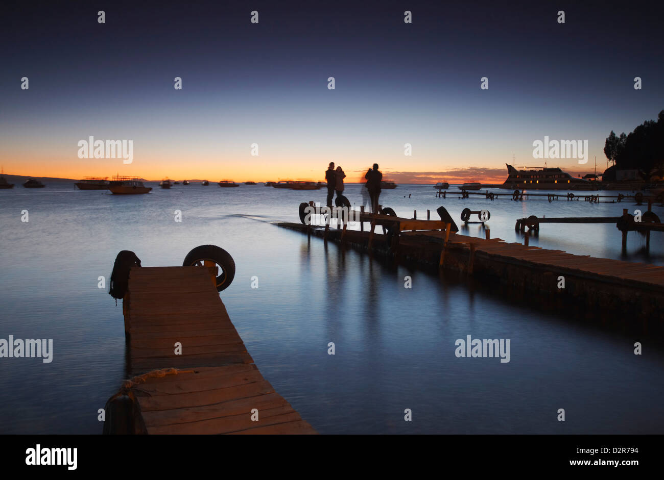 People standing on pier at sunset, Copacabana, Lake Titicaca, Bolivia, South America - Stock Image