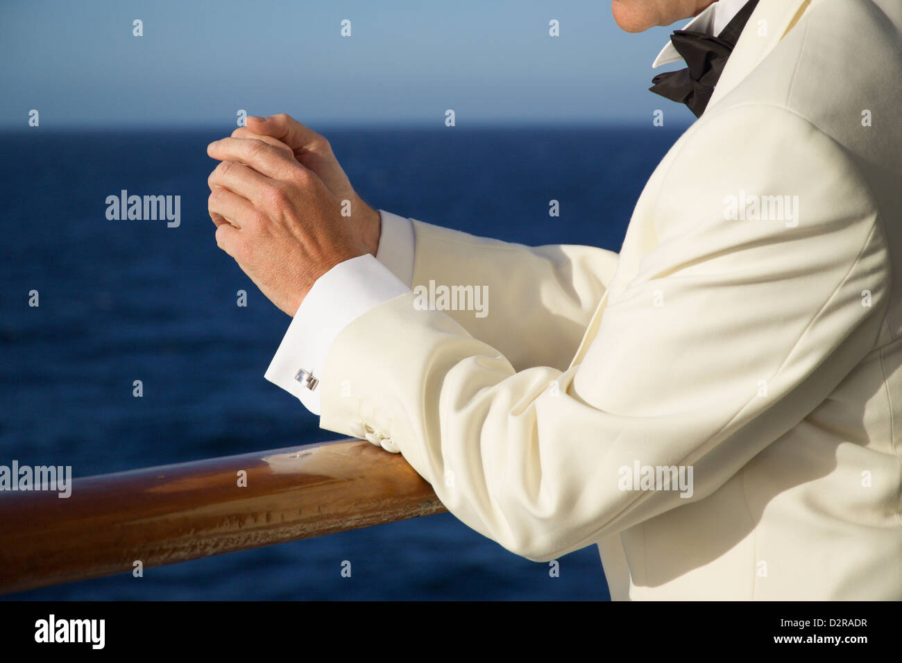 Man in Evening dress stood at the rails of a Cruise Ship - Stock Image