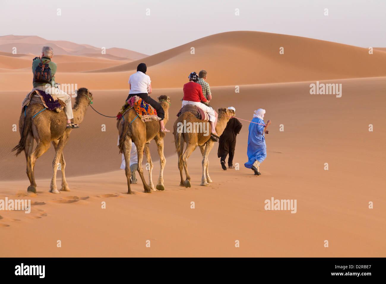 Tourists on a camel ride Merzouga Dunes Sahara Morocco Stock Photo