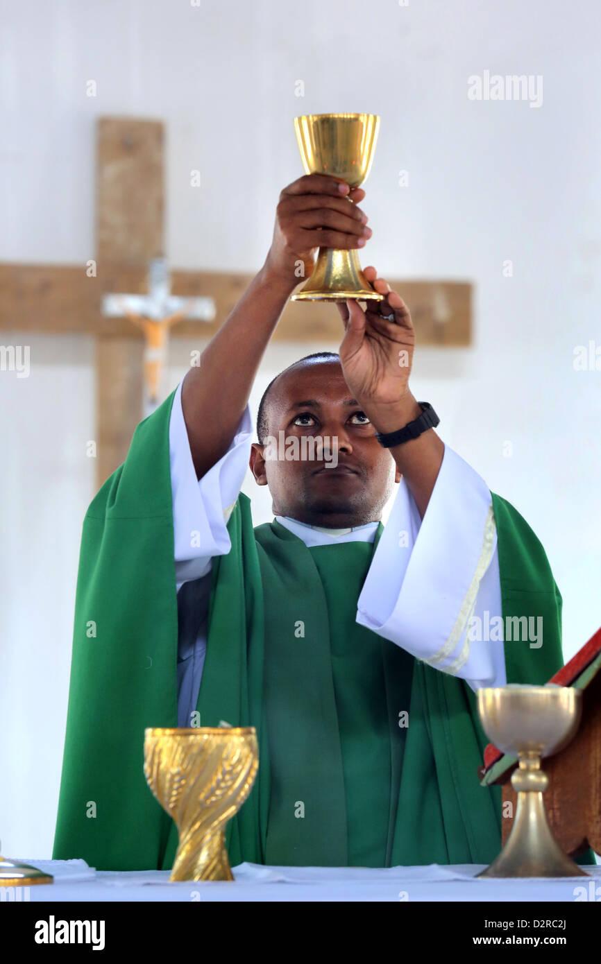 Roman catholic priest consecrating goblet during eucharist, Bagamoyo, Tanzania - Stock Image