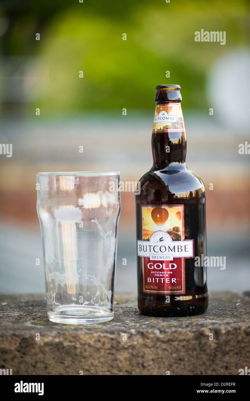 Pint glass next to a glass bottle of Butcombe Bitter - Stock Image