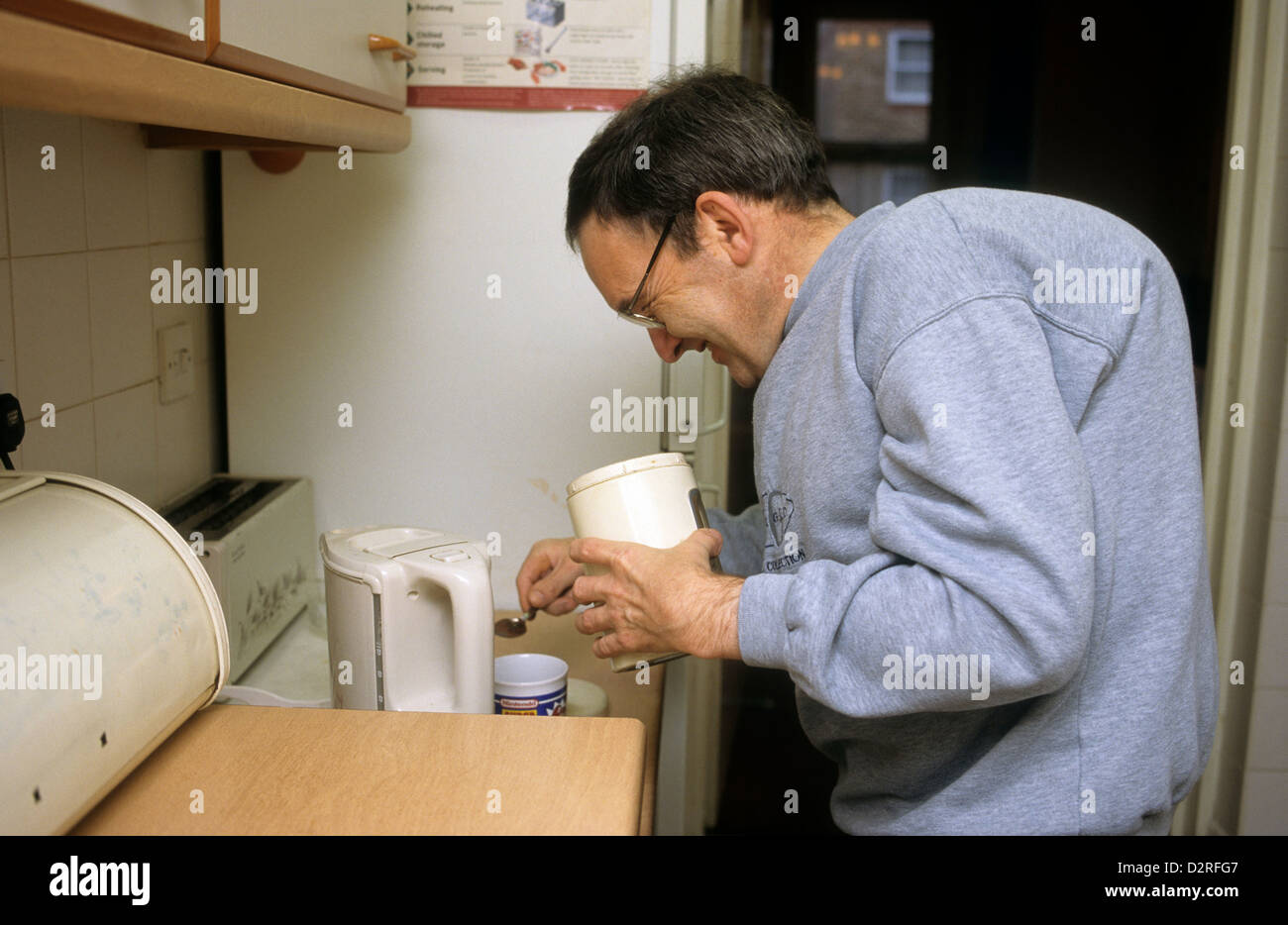 Disabled man making a cup of tea in the kitchen - Stock Image