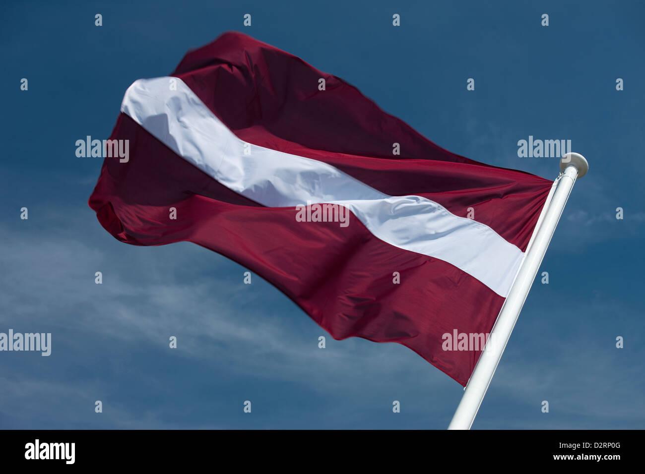 LATVIAN FLAG FLYING ON FLAGPOLE - Stock Image
