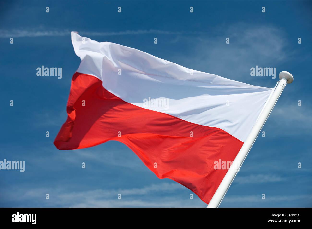 POLISH FLAG FLYING ON FLAGPOLE - Stock Image