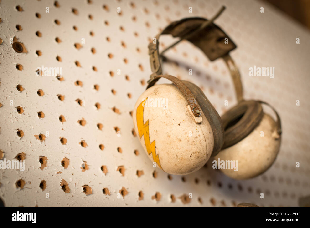 A pair of old earmuffs for hearing protection hangs on a wall. A bolt of lightning adorns the side. - Stock Image