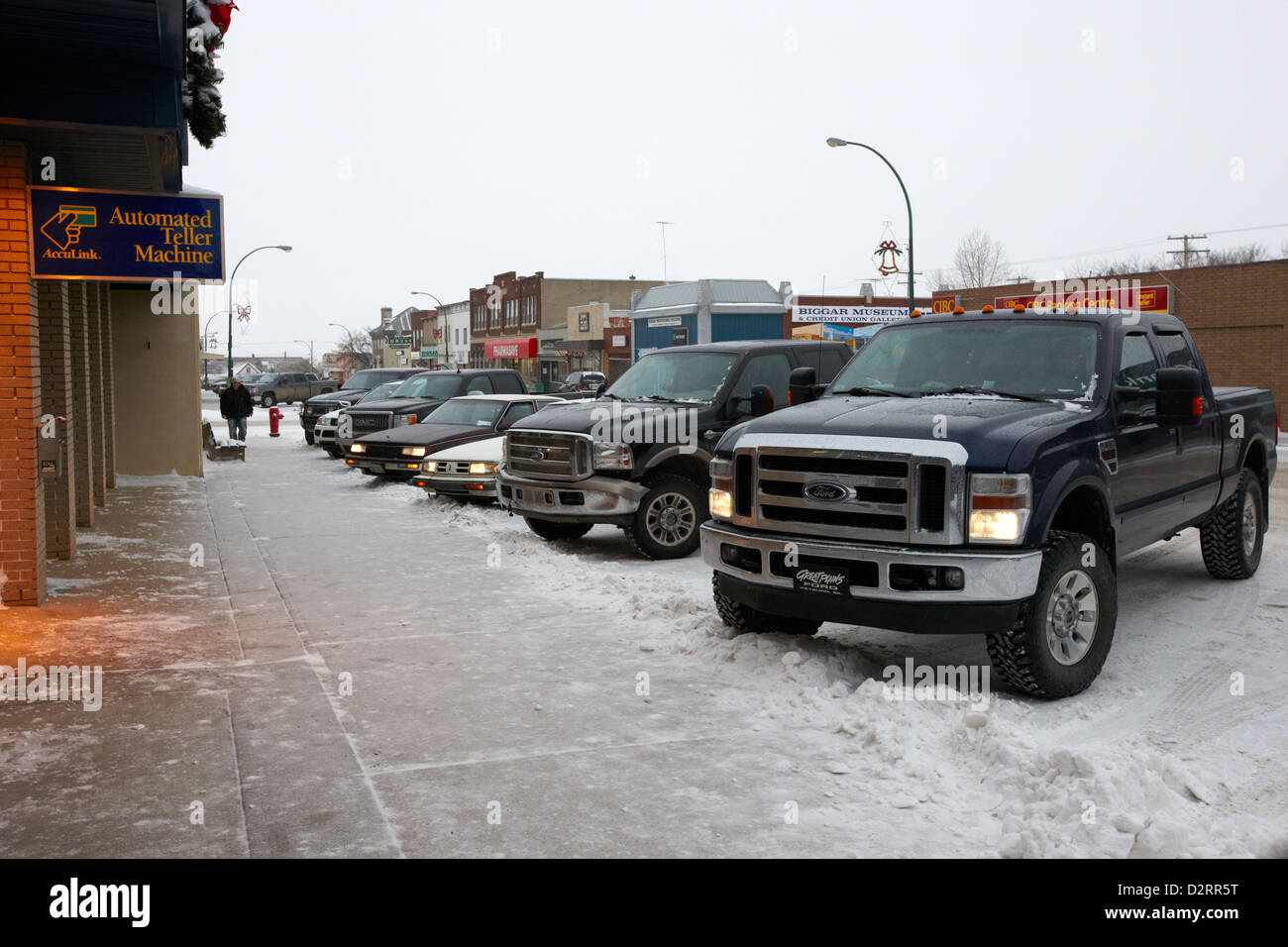 row of trucks and cars parked on the main street Biggar Saskatchewan Canada - Stock Image