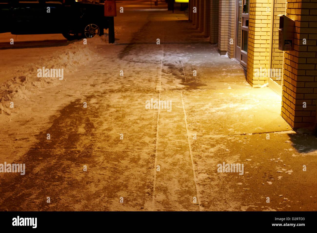 cleared sidewalk at night past shops Biggar Saskatchewan Canada - Stock Image