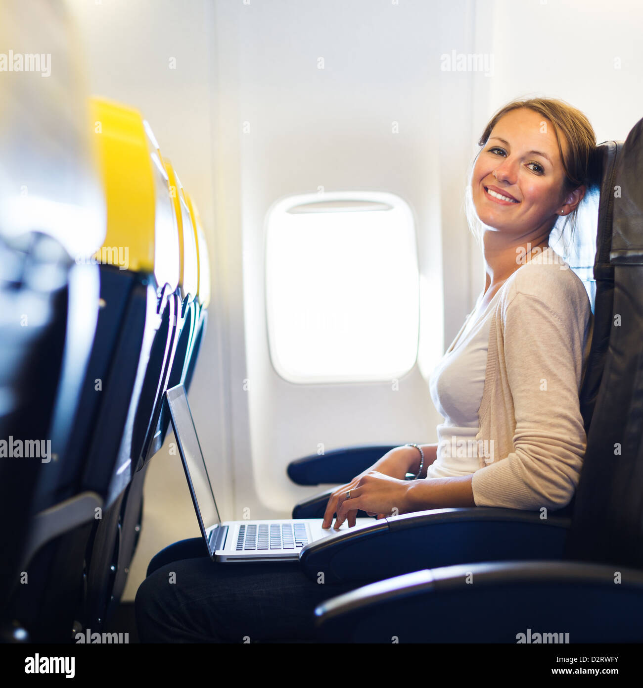 Young woman working on her laptop computer on board of an airplane during the flight - Stock Image