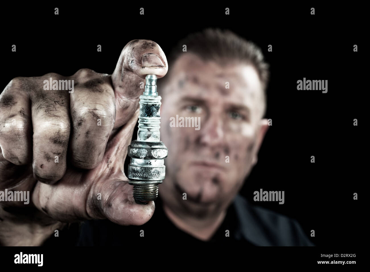 An auto mechanic shows a damaged and worn spark plug as he performs a tune up. - Stock Image