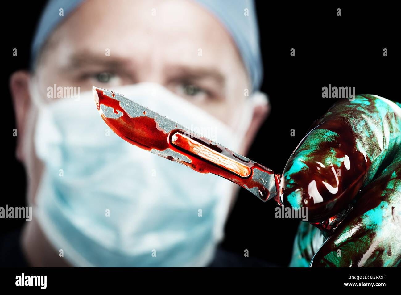 A male surgeon holds up a sharp, bloody scalpel during surgery - Stock Image